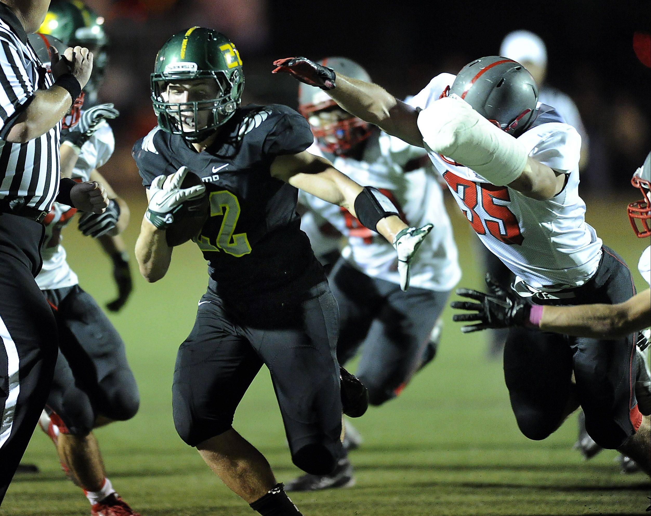 Fremd's Garrett Groot eludes Palatine's Brad Bauer for a first-quarter touchdown at Fremd on Friday.