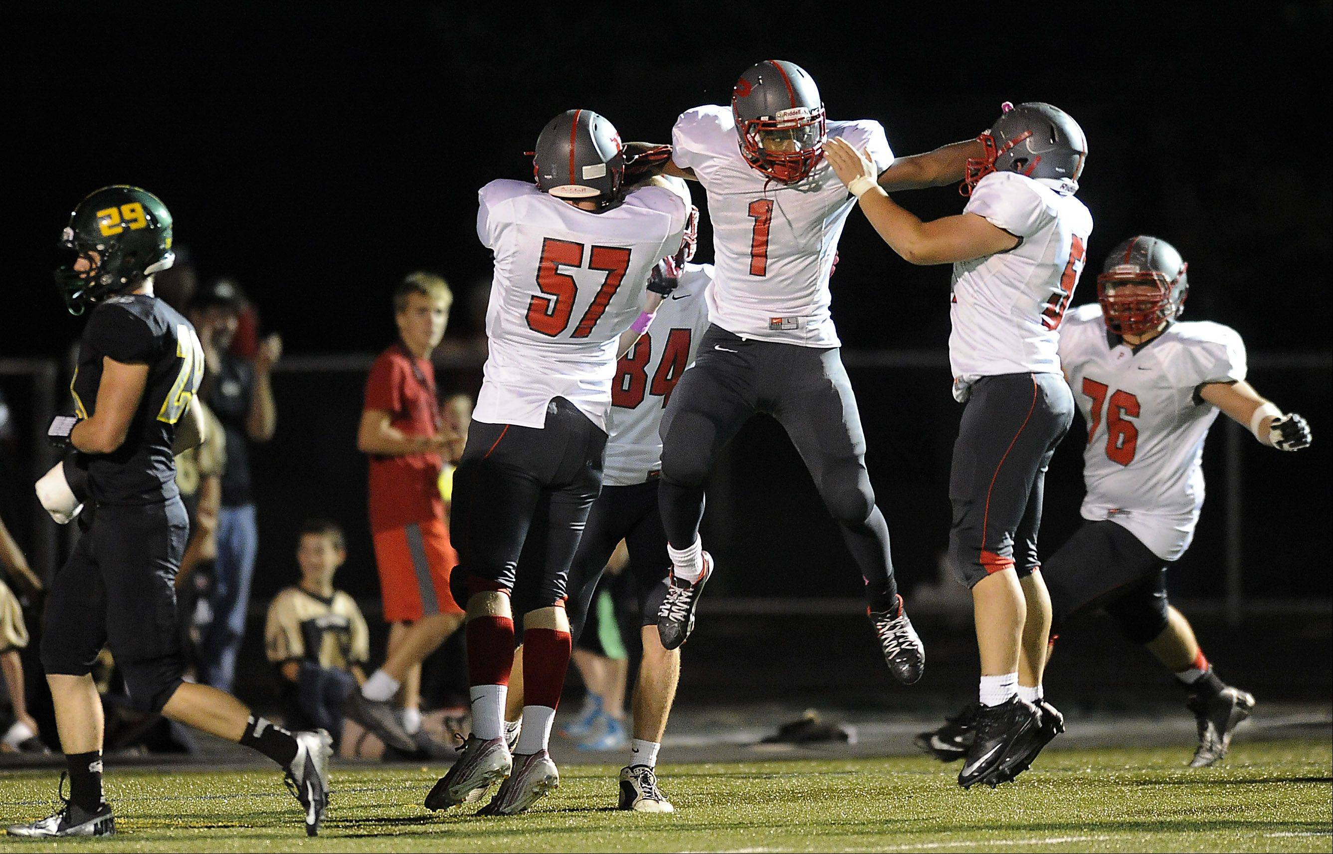 Palatine's Christopher Cornelius celebrates his second-quarter touchdown with teammates Jesus Cordova and Kevin Clark.