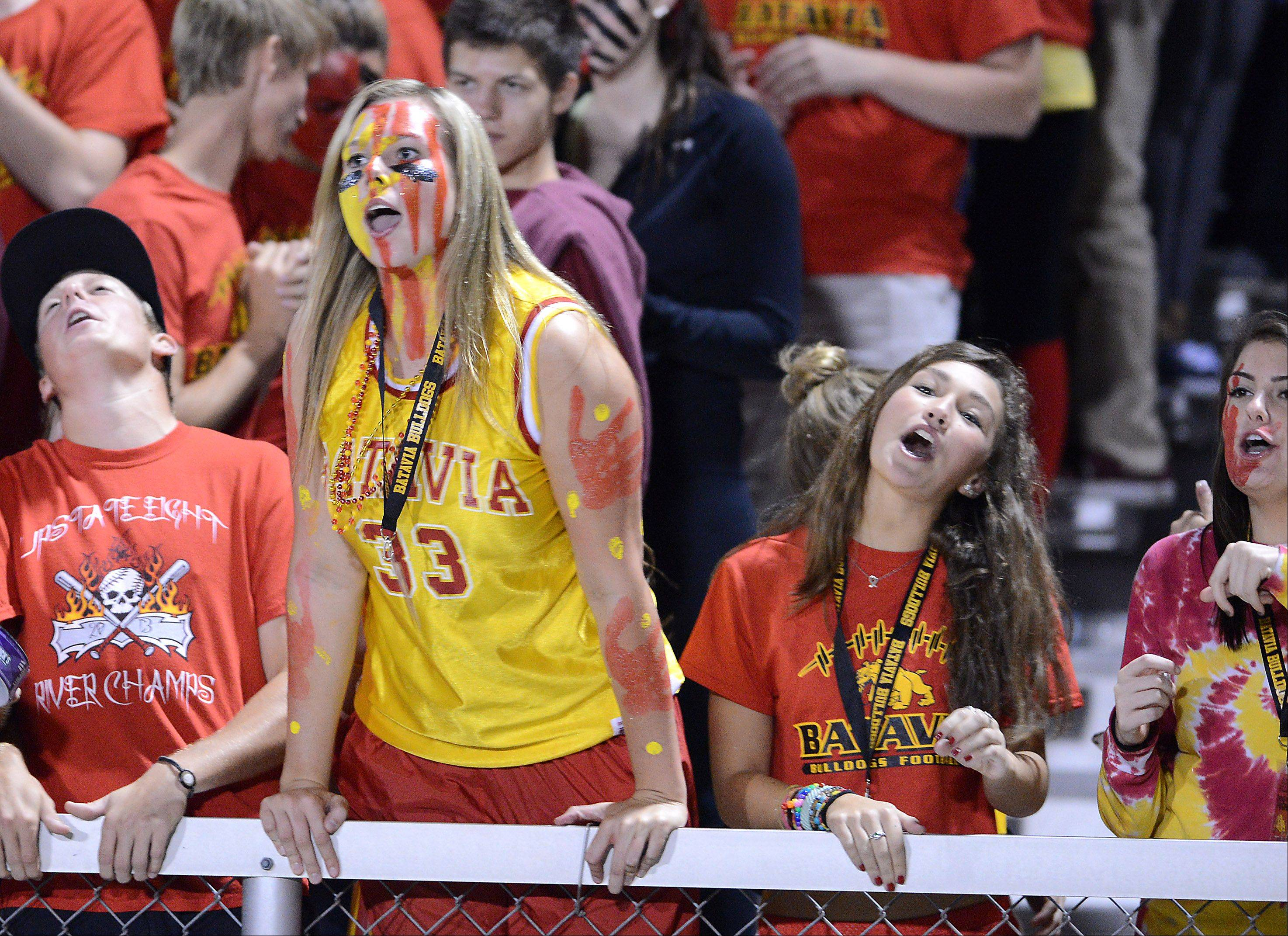 Batavia fans, including senior Erin Bayram, in yellow, cheer on the Bulldogs against St. Charles North.