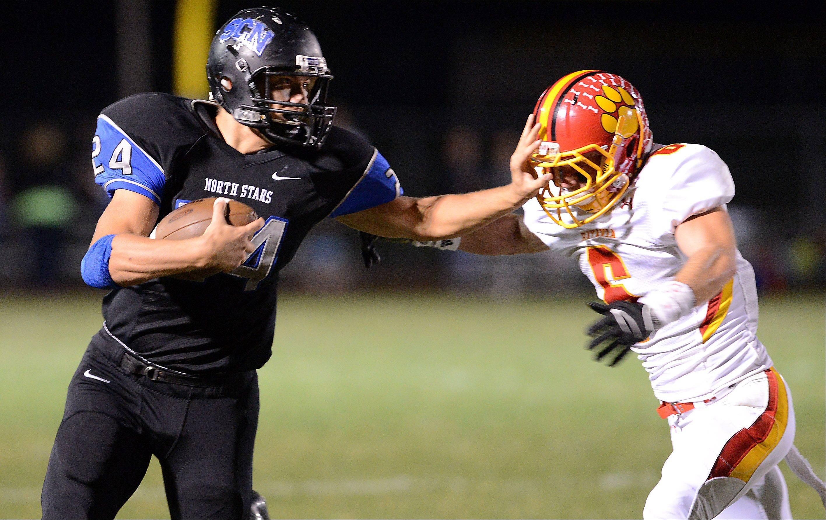 St. Charles North's Evan Kurtz stiff-arms Batavia's Rourke Mullins at the end of a 30-yard run.