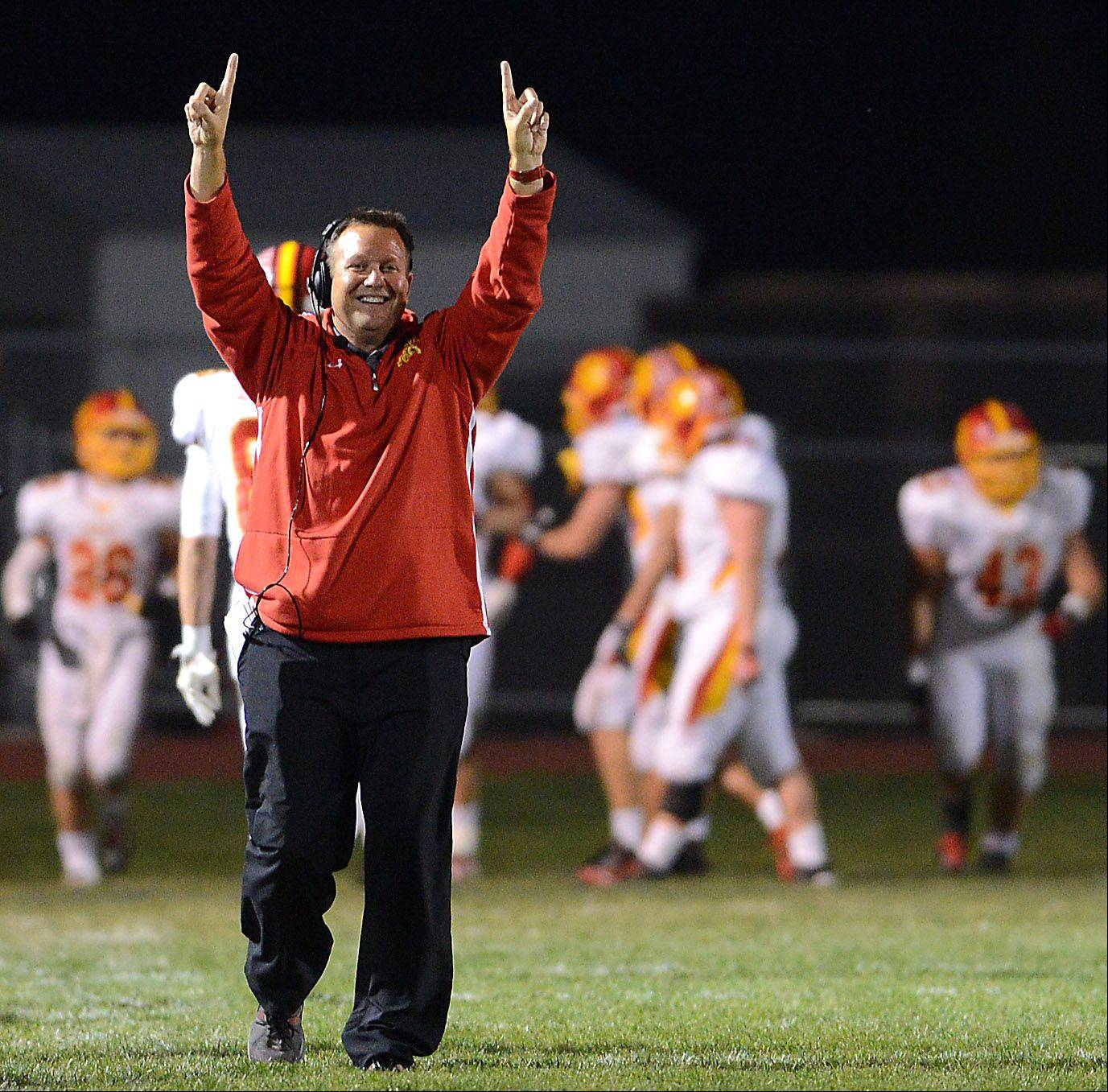 Coach Dennis Piron celebrates after Batavia's Michael Moffatt returns an interception for a touchdown to put the Bulldogs up 25-0 to close the first half.
