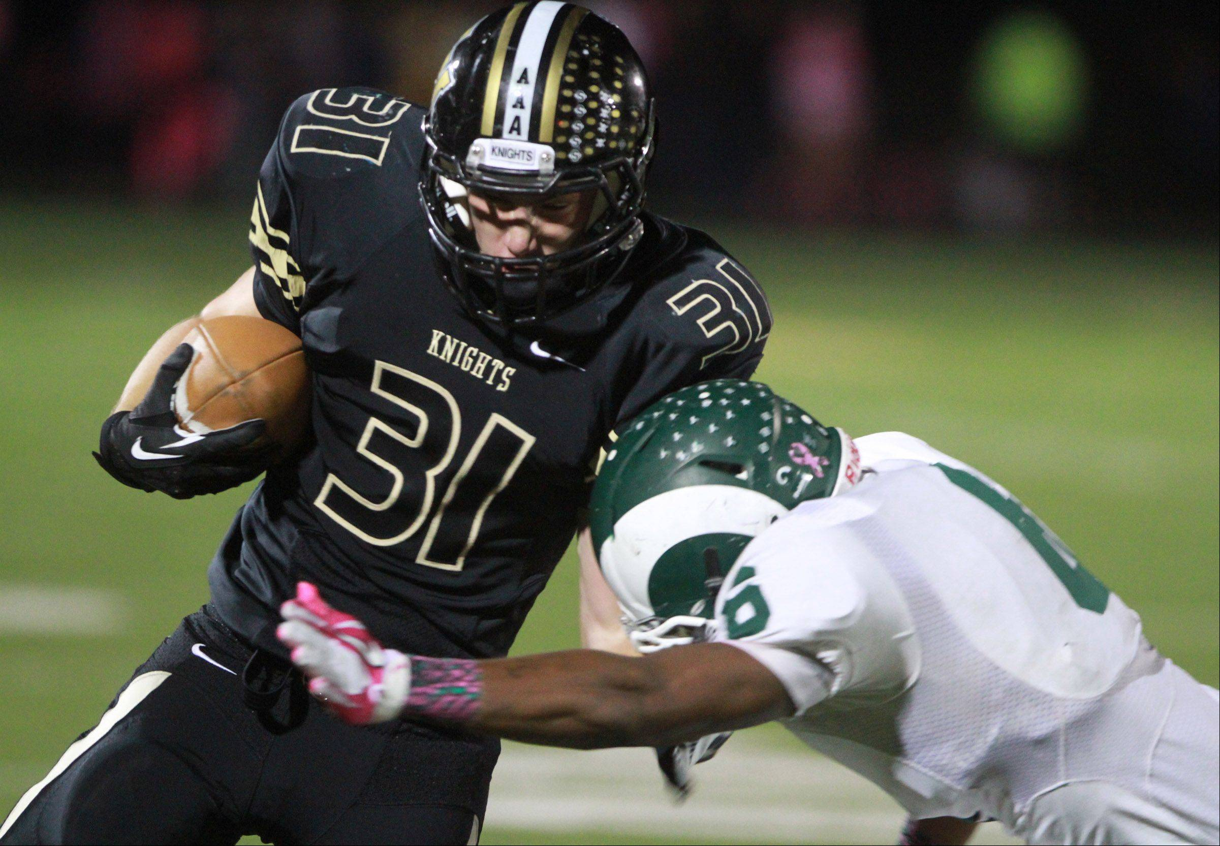 Grayslake North running back Brad Baker is pulled down by Grayslake Central linebacker Malcolm Reed.