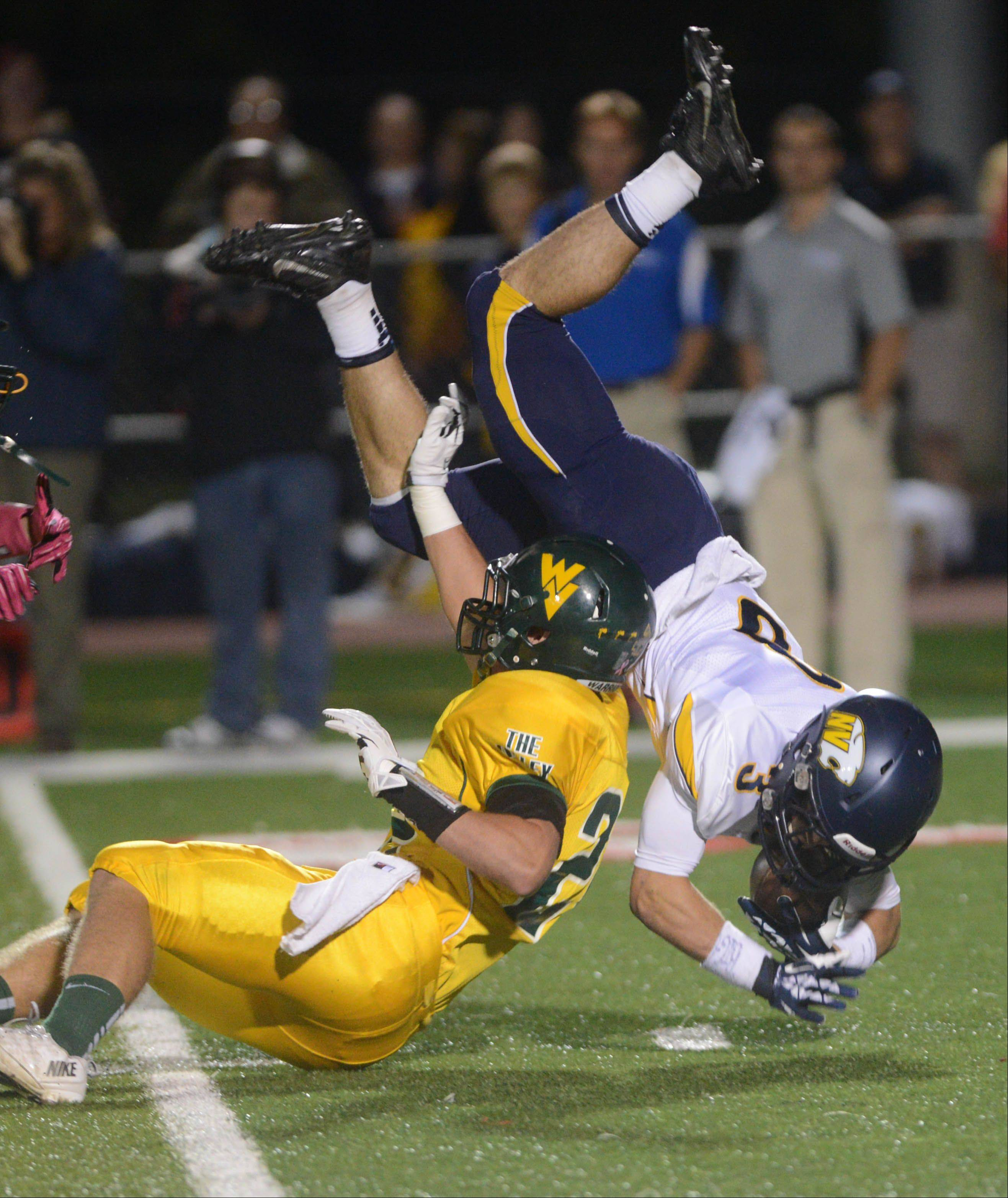 Mikey Dudek of Neuqua Valley goes airborne as Hugh Griffin of Waubonsie Valley makes a hit.