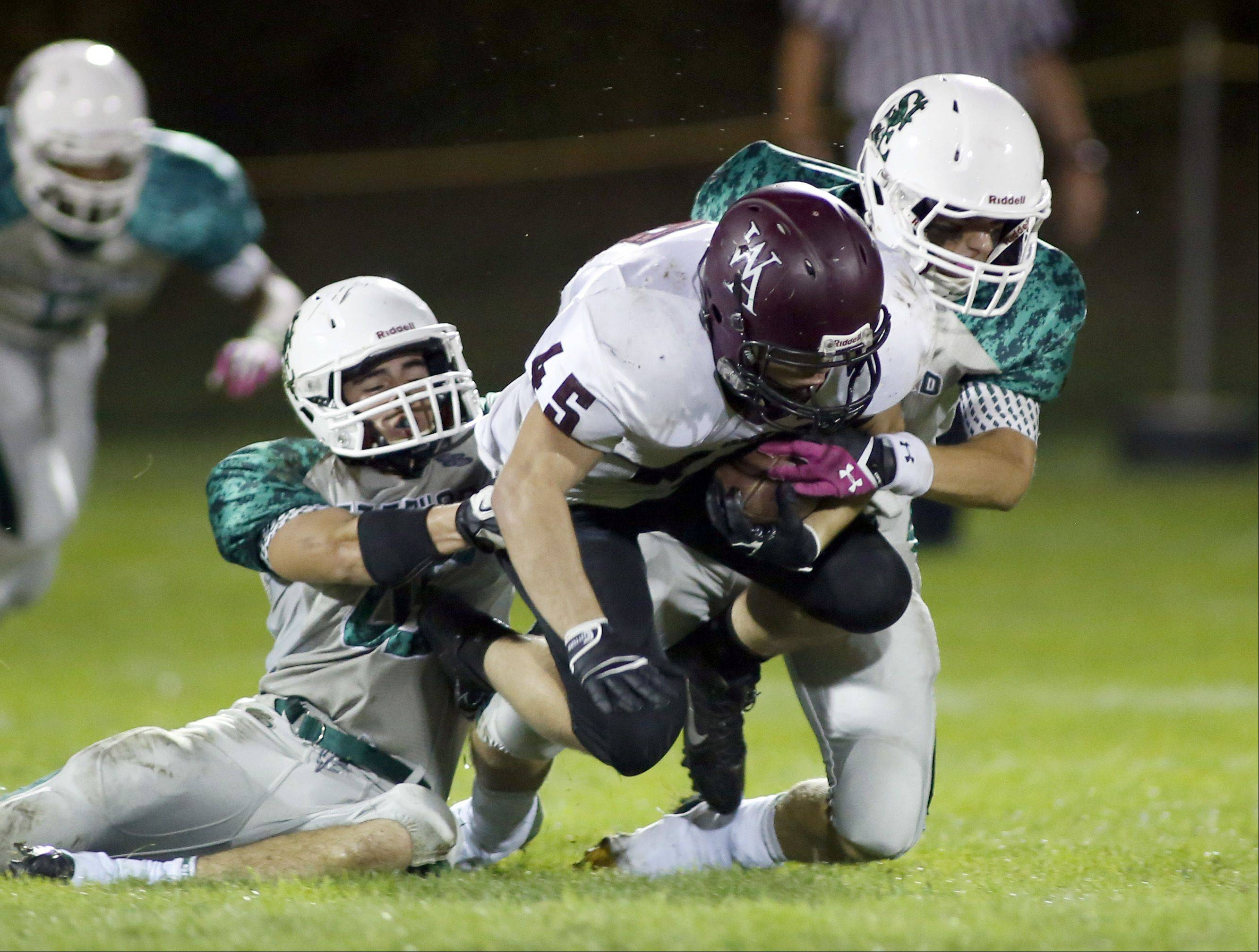 Wheaton Academy's John Gemmel tries to get extra yardage as St. Edward's William Bothwell and Matthew Colasuono reel him in .