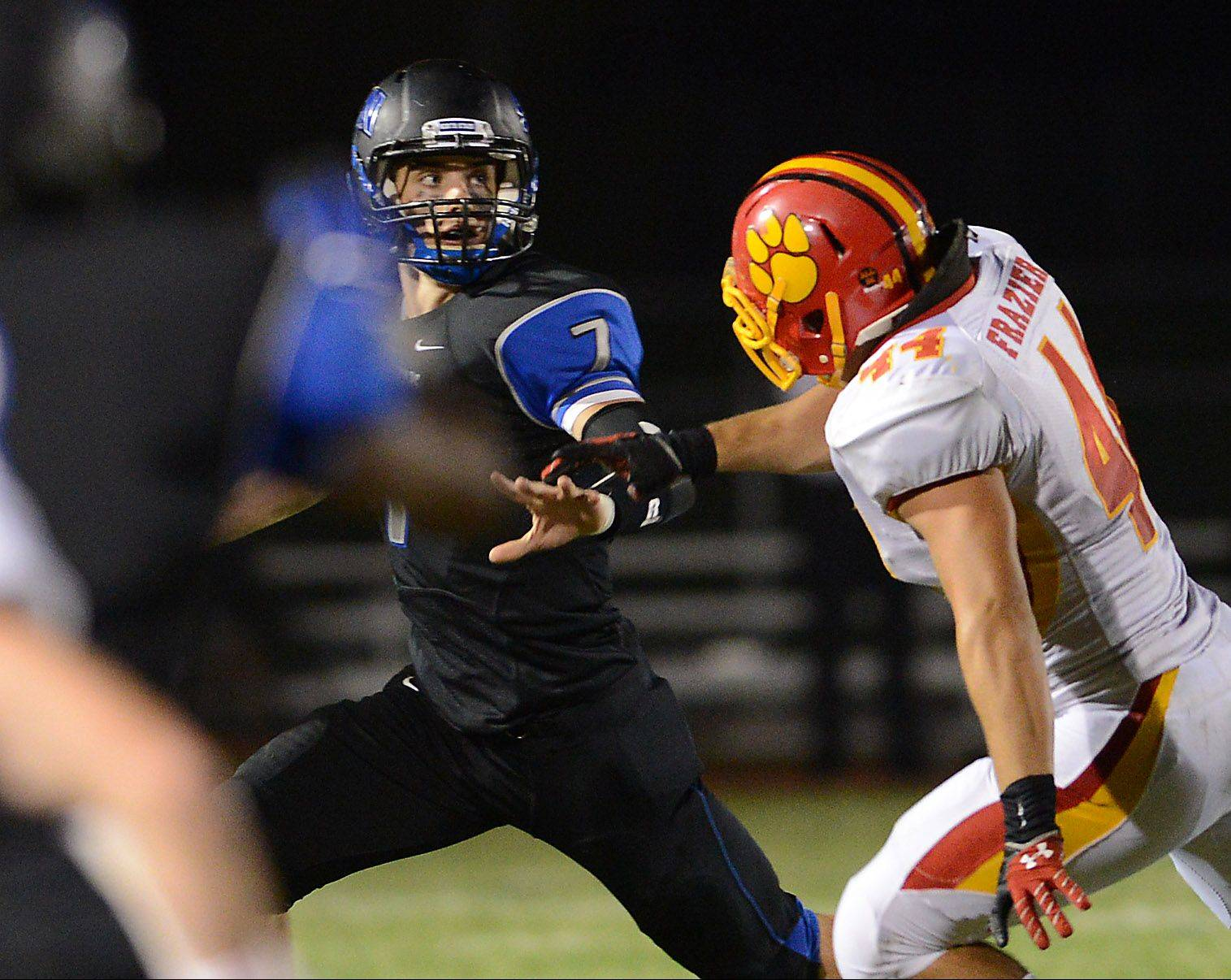 Batavia's Noah Frazier pressures St. Charles North quarterback Erik Miller during the Bulldogs' 44-7 win last Friday. Batavia's victory clinched its 10th playoff berth in the last 11 years while the North Stars need to win their final two games to become playoff eligible.