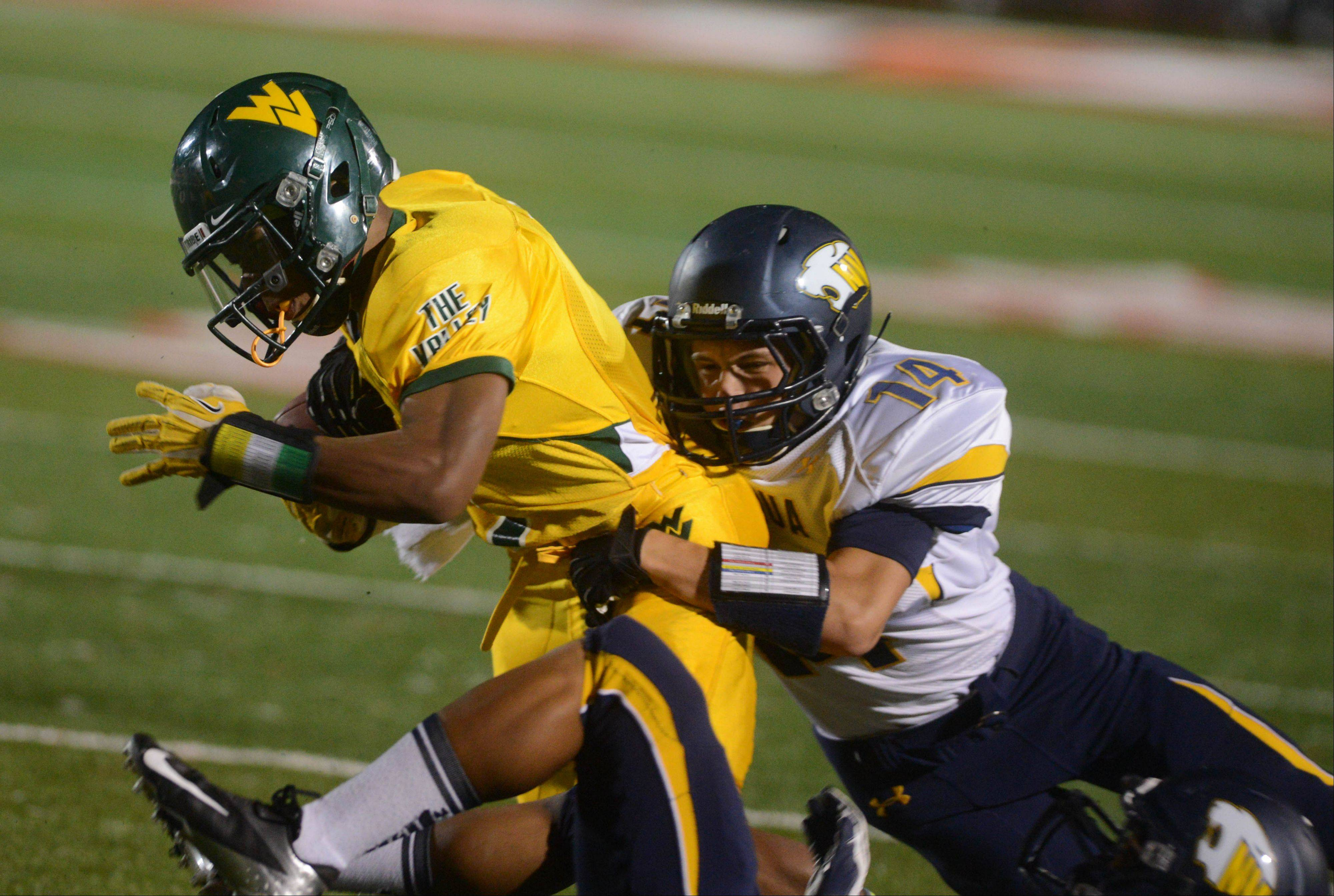 Tony Durns of Waubonsie Valley is nailed by Eli Tappin of Neuqua Valley during the Neuqua Valley vs. Waubonsie Valley football game at North Central College Friday.