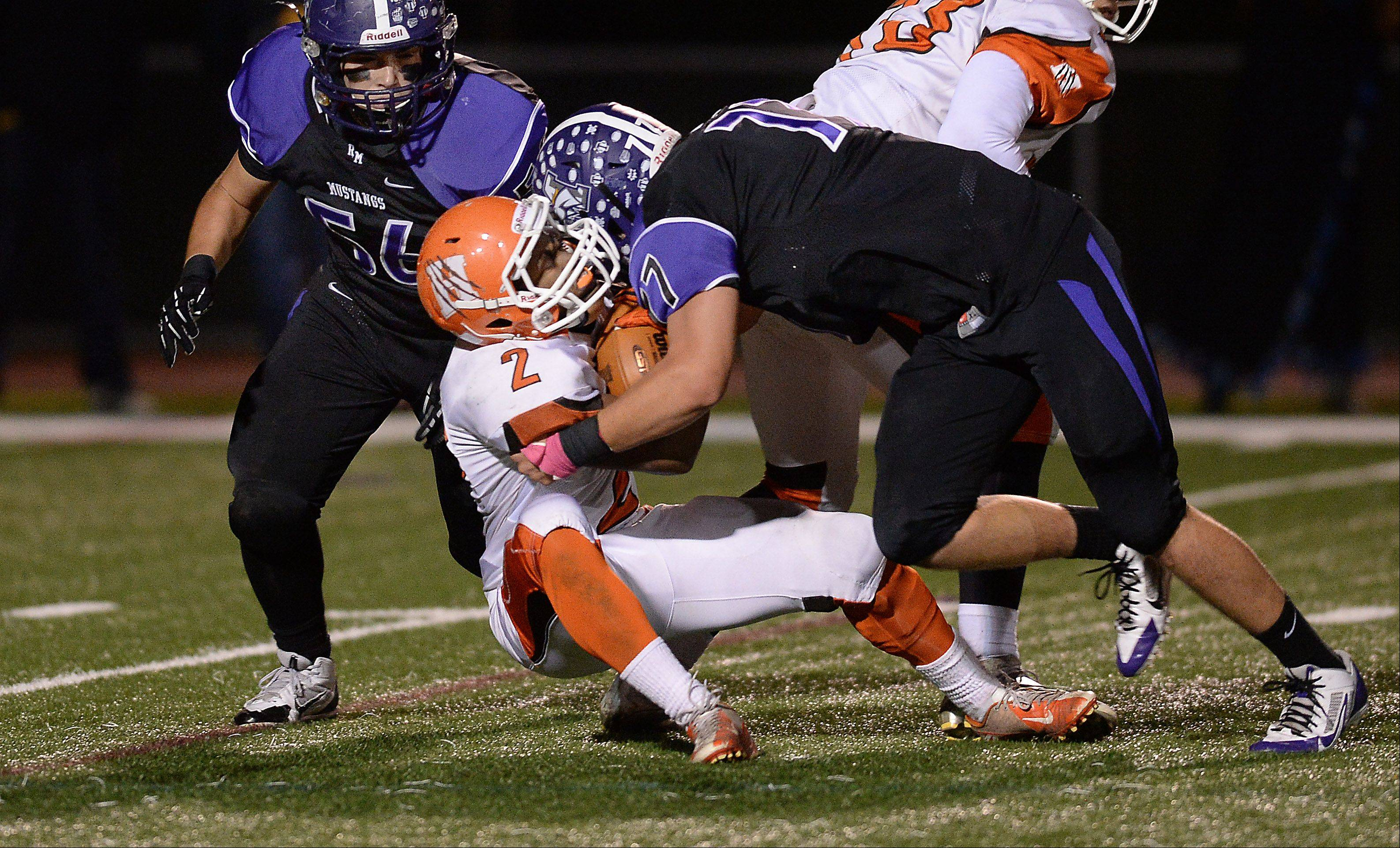 Rolling Meadows' Matt Long stops Hersey's Mario Thomas in his tracks in the second quarter in the varsity football matchup at Rolling Meadows High School on Friday.