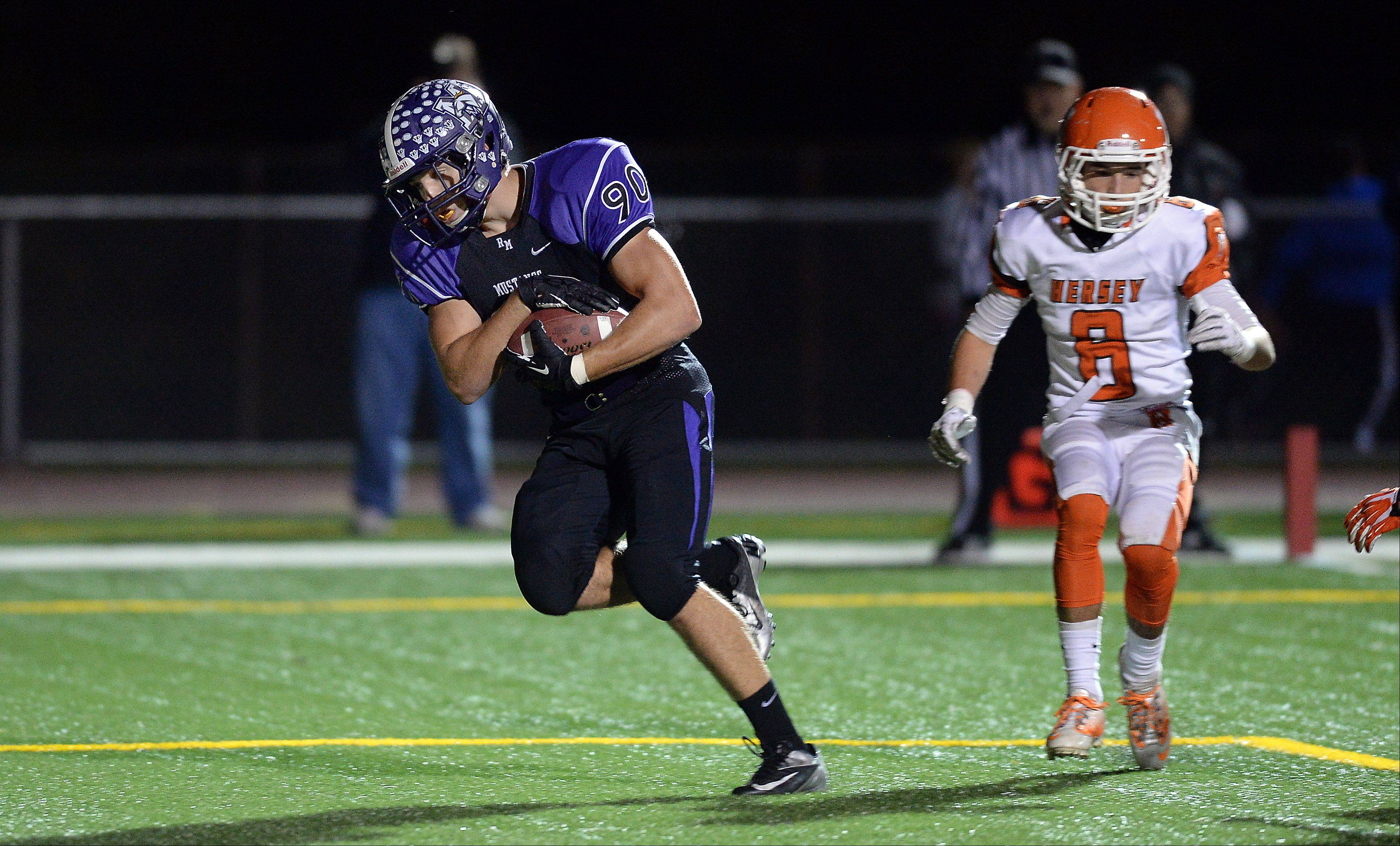 Rolling Meadows' Matt Campbell, on a pass play in the first quarter, runs in a touchdown past Hersey's Cole Monckton.