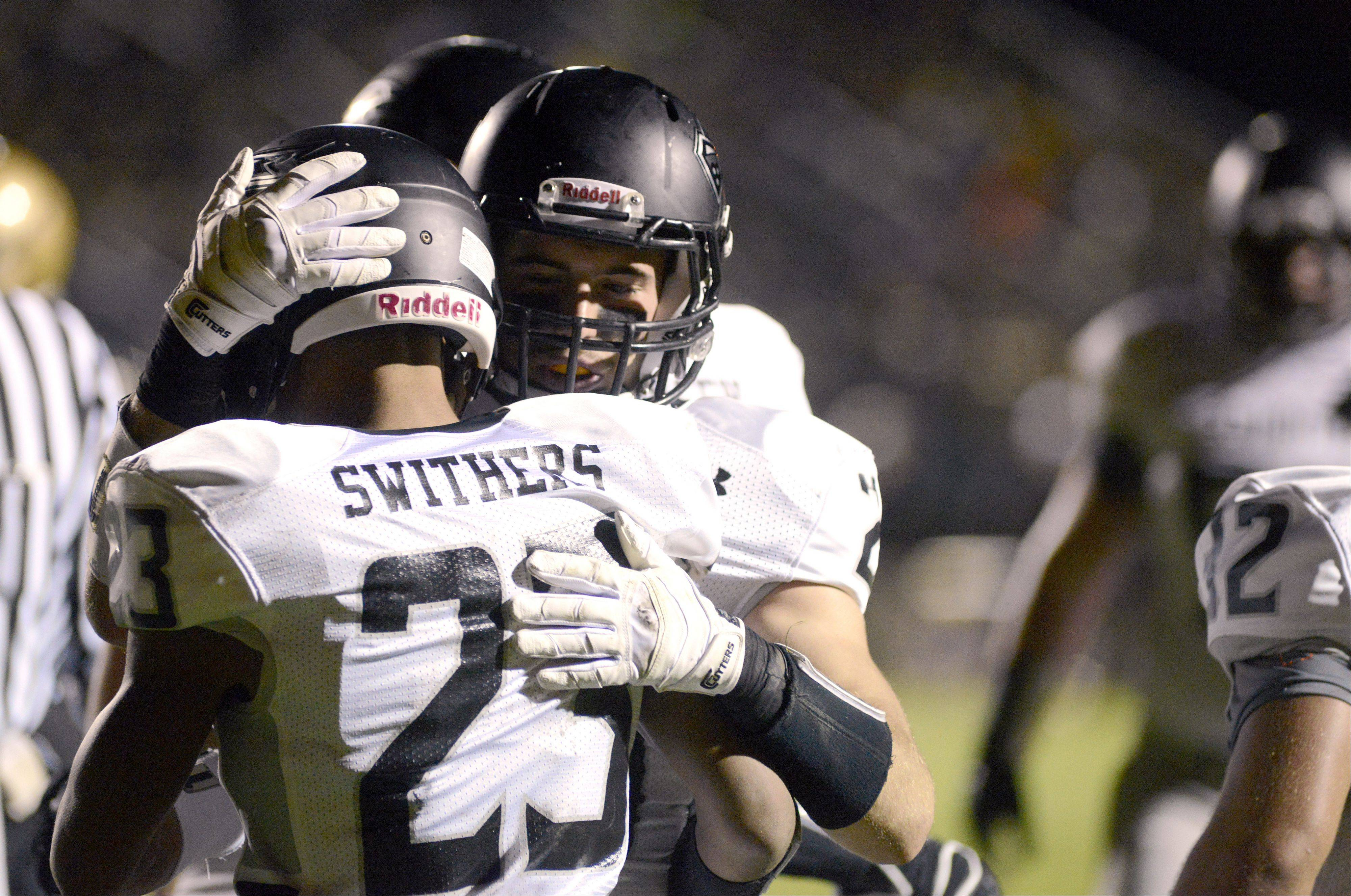 Kaneland's Isaac Swithers receives congratulations from teammate Dylan Nauert after scoring a touchdown.