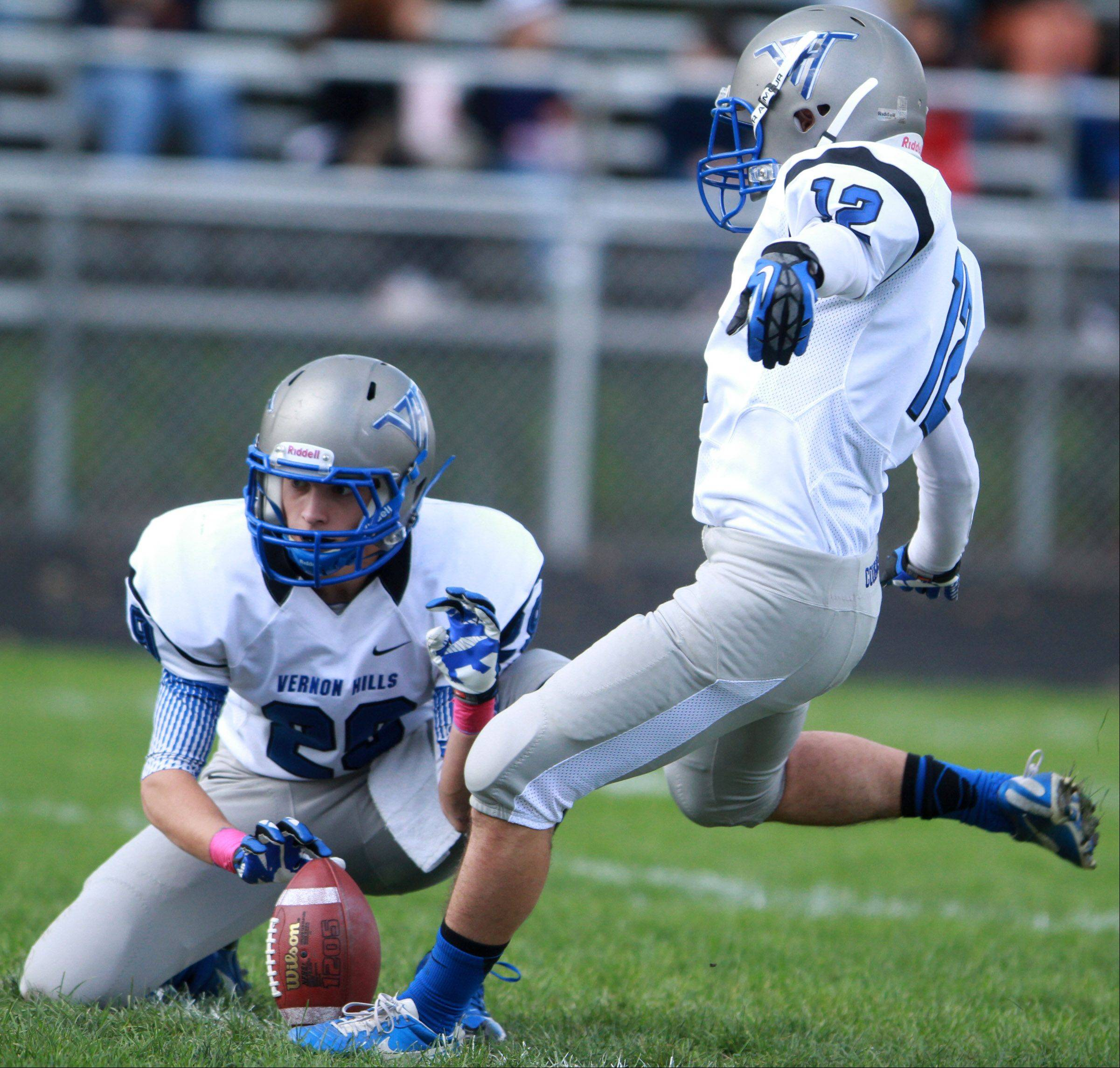 Vernon Hills kicker Jeremy Cohen kicks an extra point with Mike Mariella holding against Round Lake defender at Round Lake on Saturday, October 19.