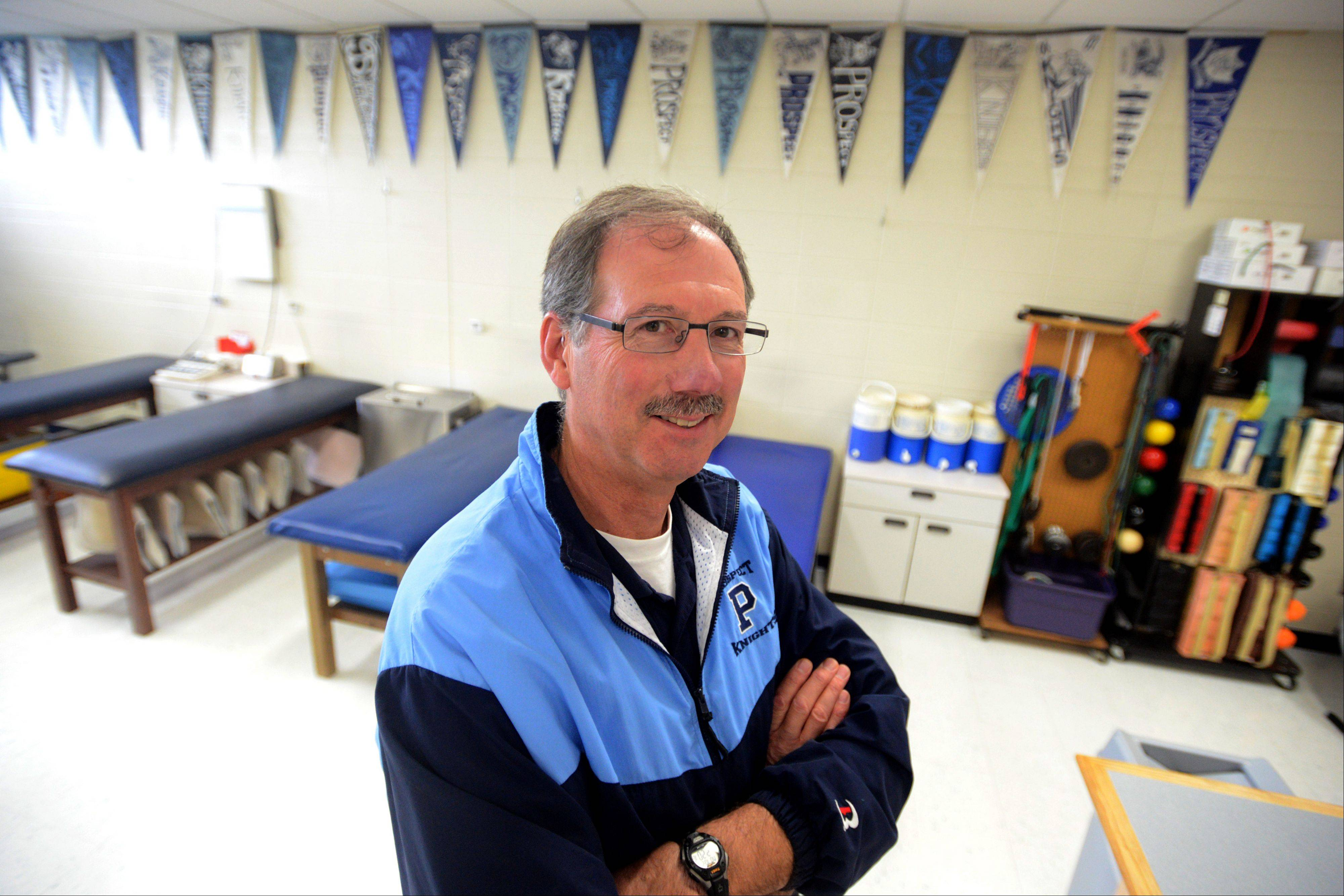 Prospect athletic trainer Matt Guth will be honored at this weekend's football game against Elk Grove for his many years of service. On the wall of the training room behind him are Prospect pennants Guth has collected over the decades.