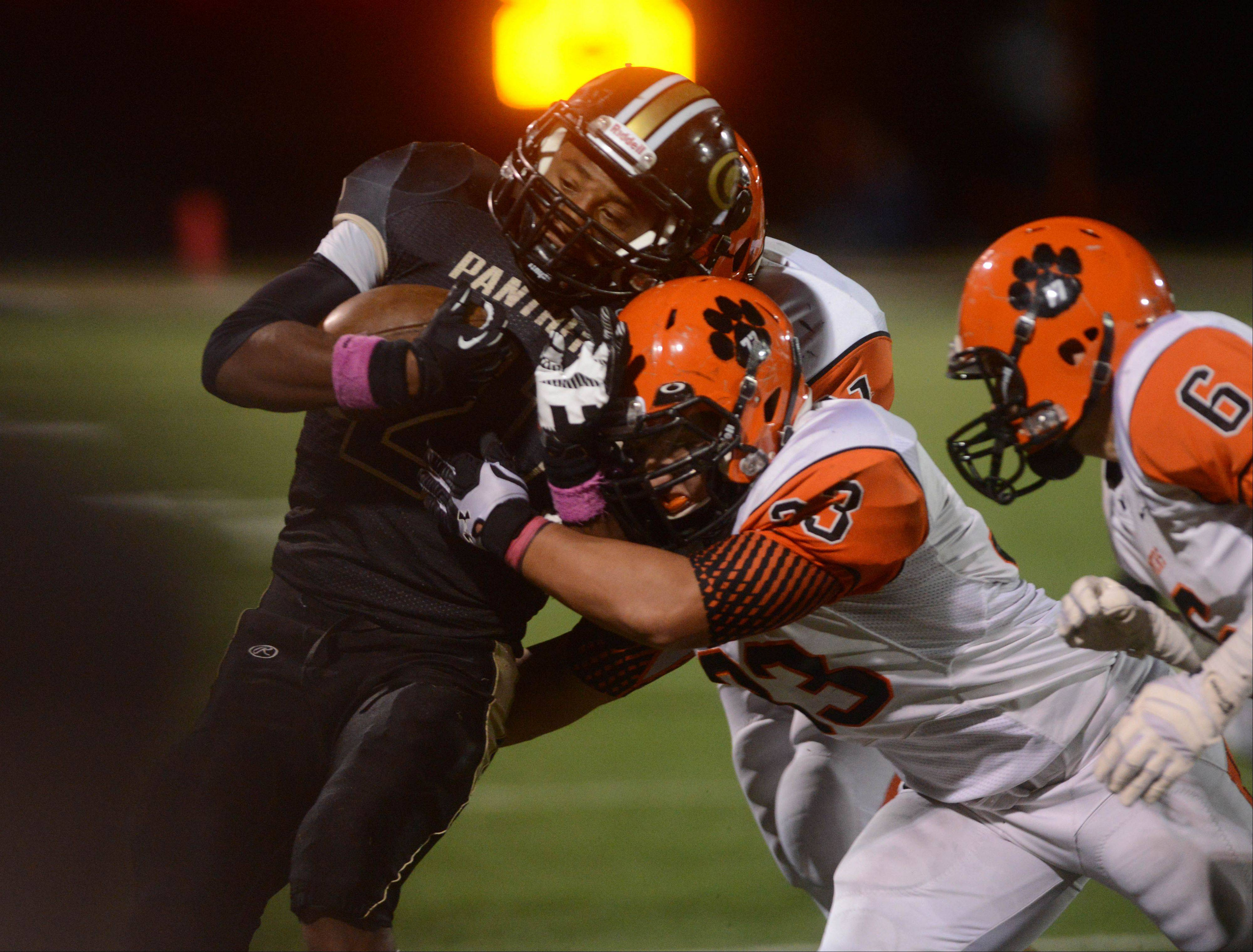 Justin Jackson of Glenbard North is pulled down by Jake Kyllonen of Wheaton Warrenville South during the Wheaton Warrenville South at Glenbard North football game Friday.