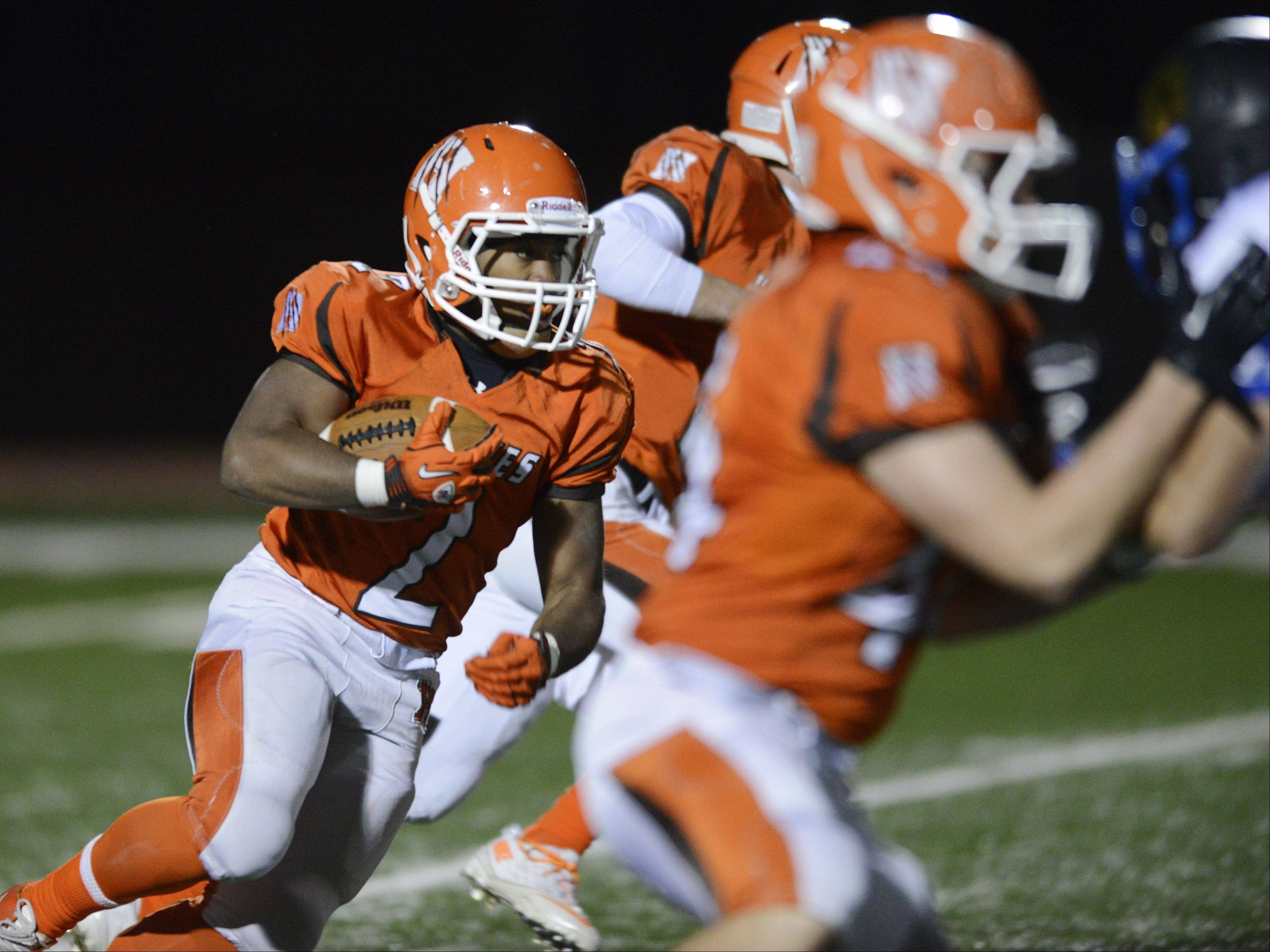 Hersey's Mario Thomas carries the ball for a touchdown on the first play from scrimmage to start the third quarter against Wheeling on Friday.