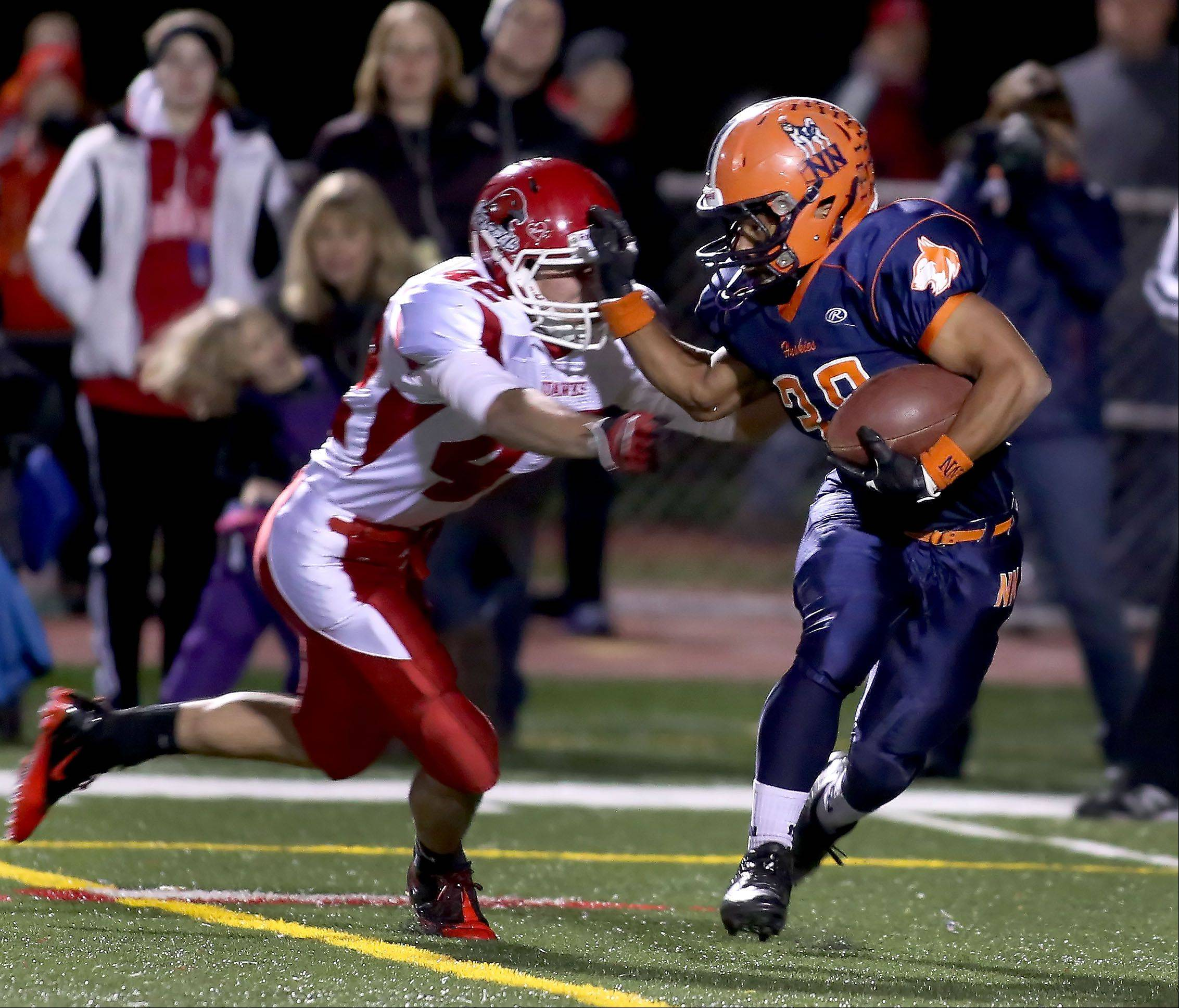 Daniel Spaccapaniccia of Naperville Central moves in to tackle Adam Milsap of Naperville North.