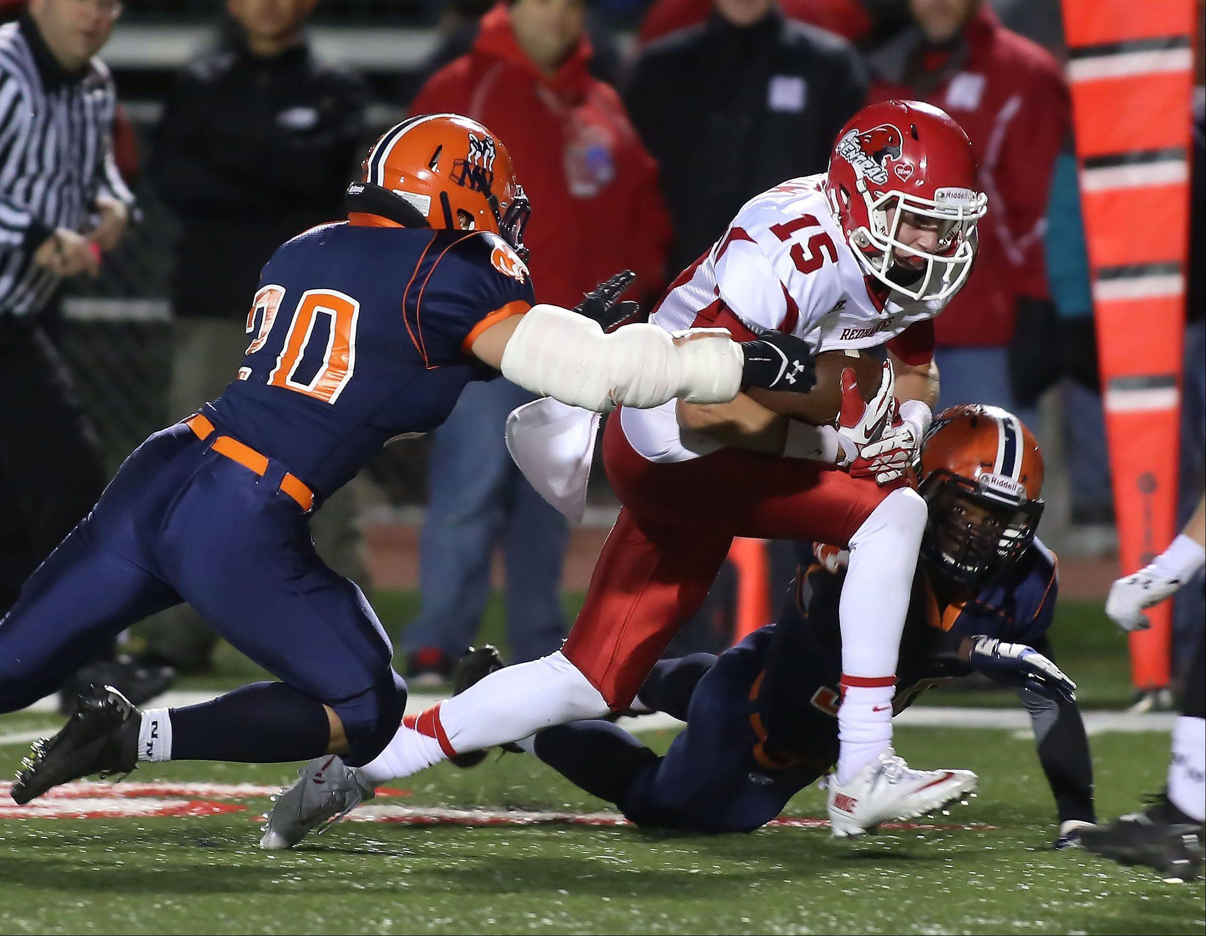 Michael Kolzow of Naperville Central moves the ball through the Naperville North defense.