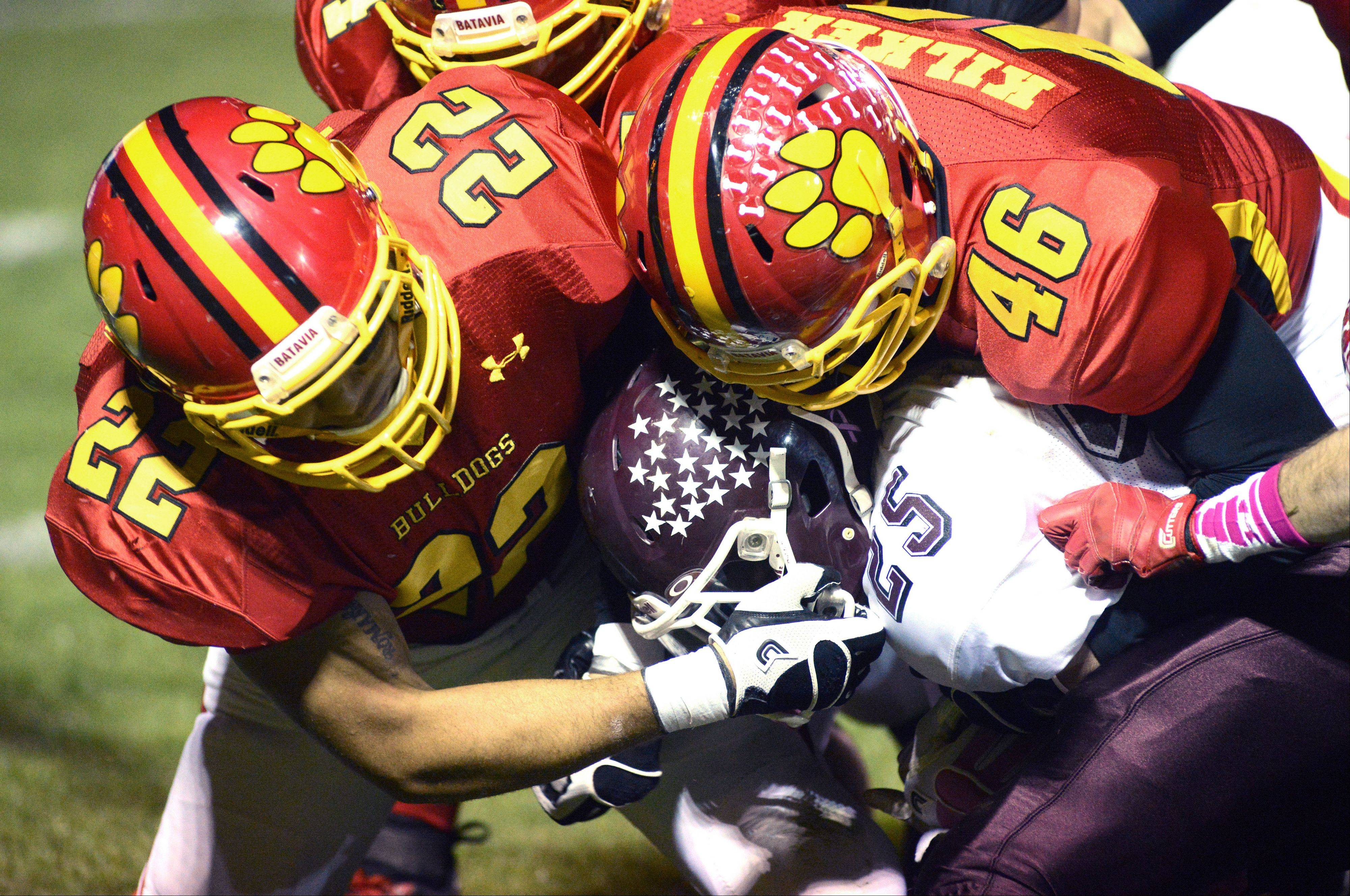 Elgin's Johnny Higgins is slammed to the ground by Batavia's Anthony Thielk and Donovan Kilkerin the first quarter.