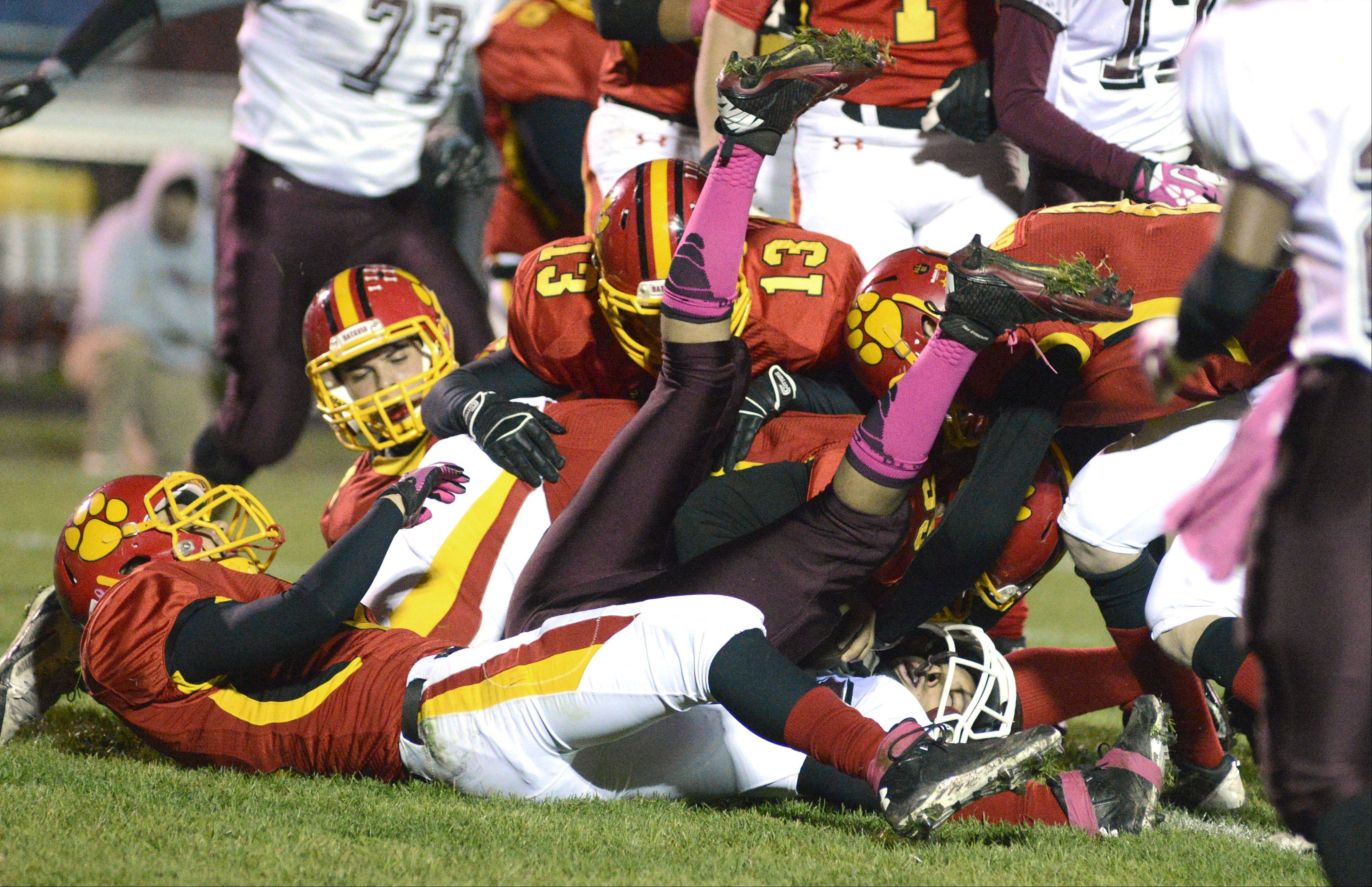 A pack of Batavia Bulldogs takes down Elgin's Jesse James sending his feet into the air in the first quarter on Friday, October 25.