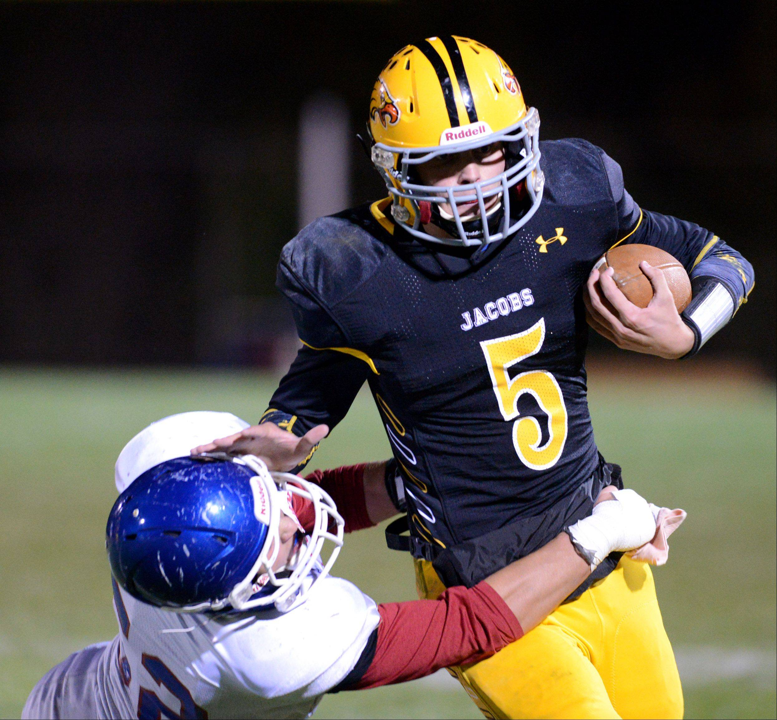 Jacobs' Bret Mooney stiff-arms Dundee-Crown's Zach Thelen.