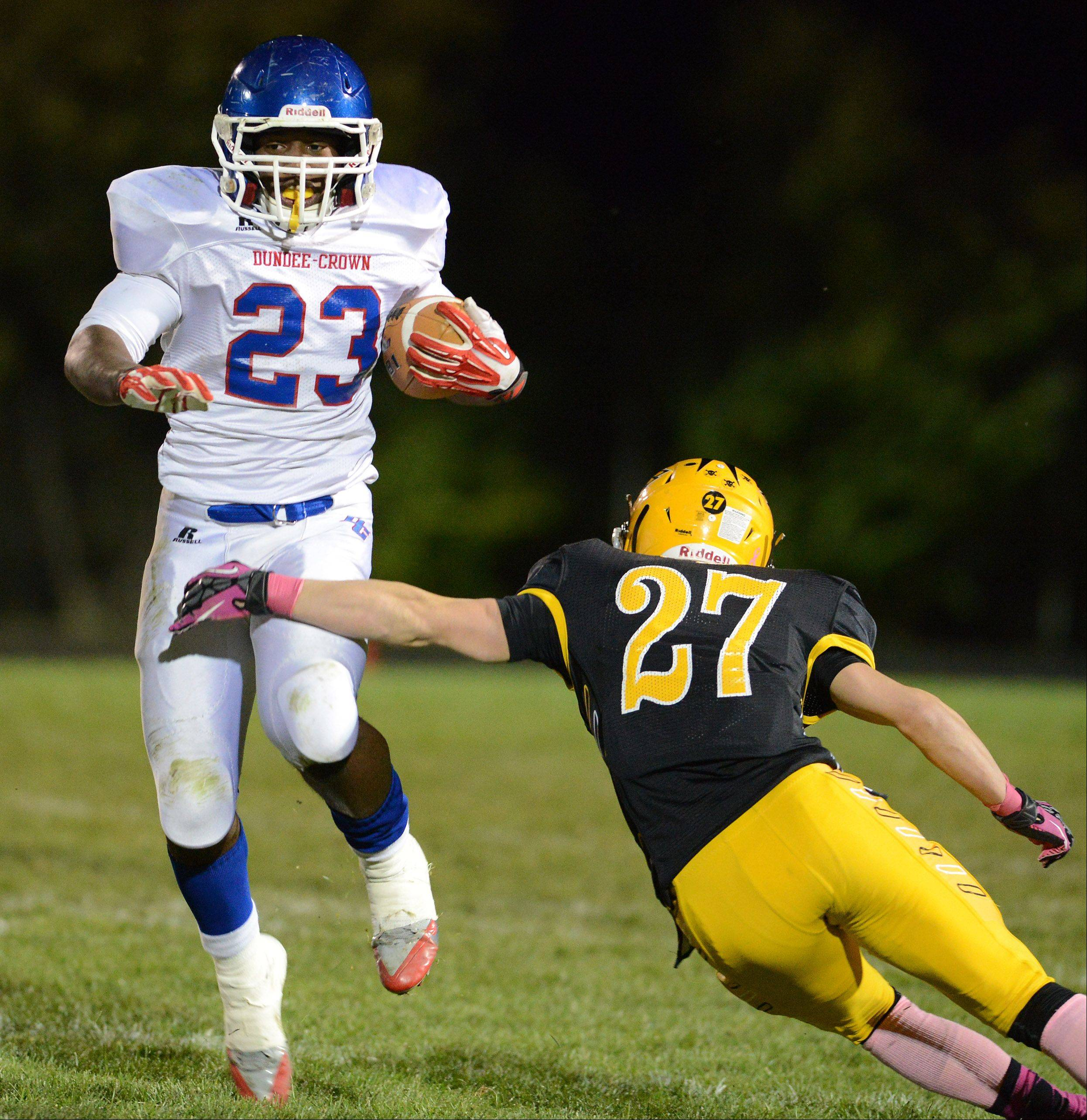 Dundee-Crown's Cordero Parson (23) sidesteps Jacobs' Josh Narvaez (27) on a third-quarter run during Friday's game in Algonquin. Dundee-Crown hits the road to Oak Park-River Forest for the first round of the Class 8A playoffs, while Jacobs will host Conant in Class 7A.