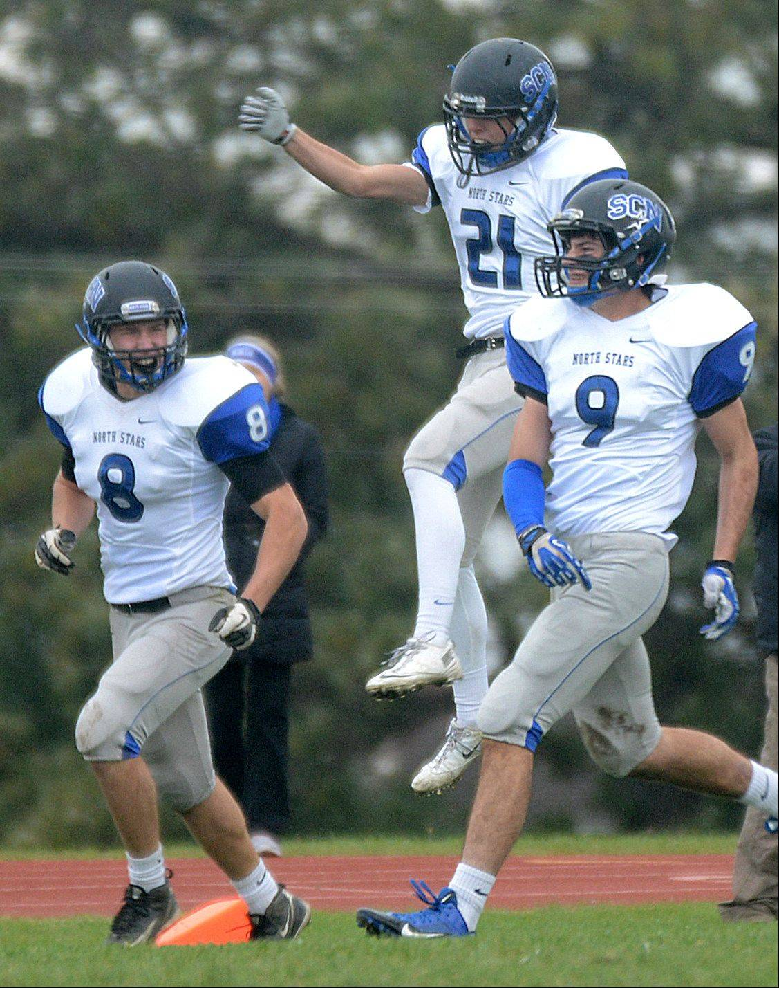St. Charles North's, from left, Nick Drawant, Dylan Hunter, and Cameron MacKenzie celebrate a touchdown which was scored on a South Elgin fumble in the end zone.