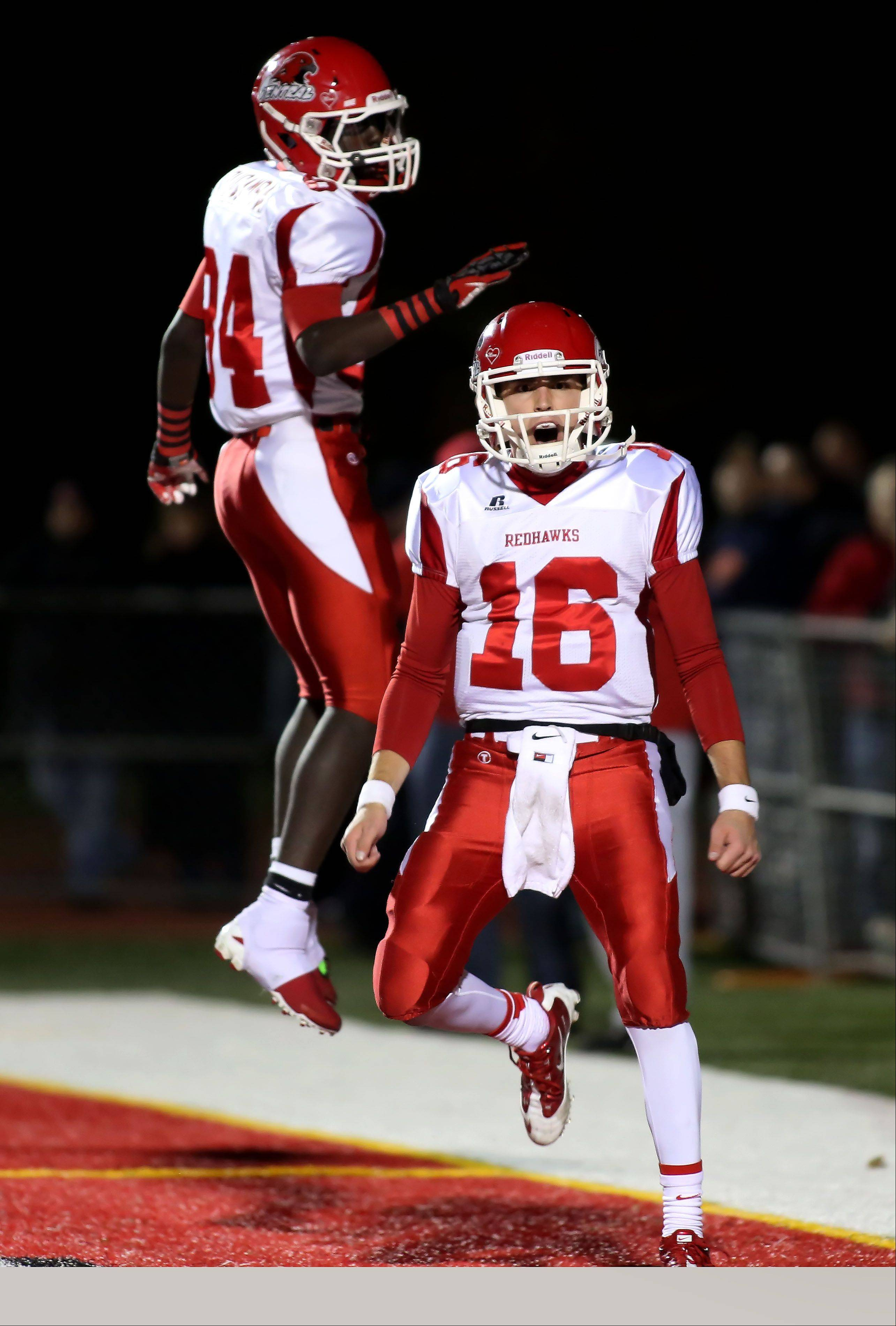 Quarterback Jake Kolbe, right, of Naperville Central celebrates with Emmanuel Rugamba after scoring a touchdown in the first quarter against Naperville North on Friday at North Central College.