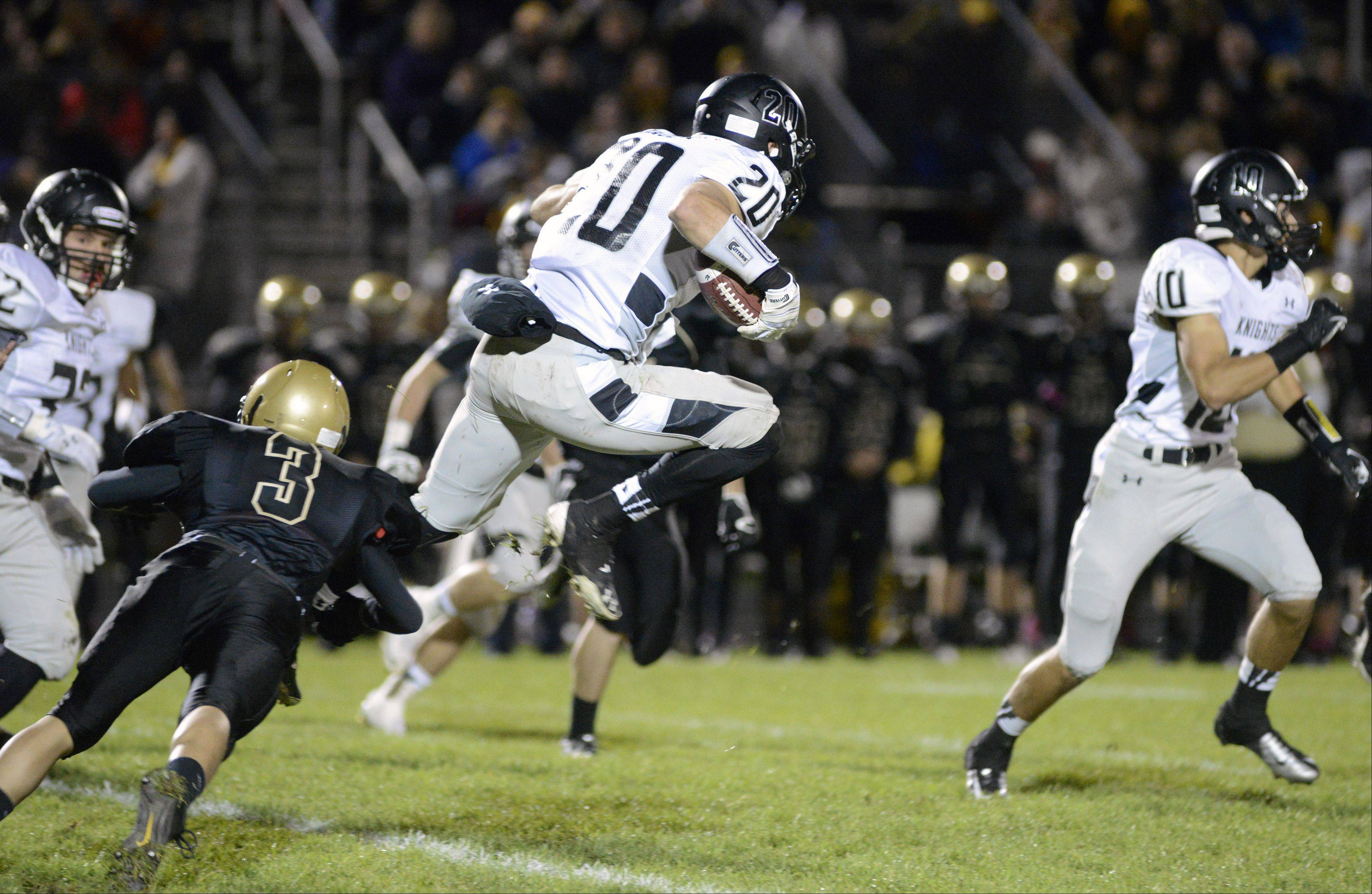 Kaneland's Dylan Nauert leaps out of the grasp of Sycamore's Edgar Garcia in the second quarter on Friday, October 18.
