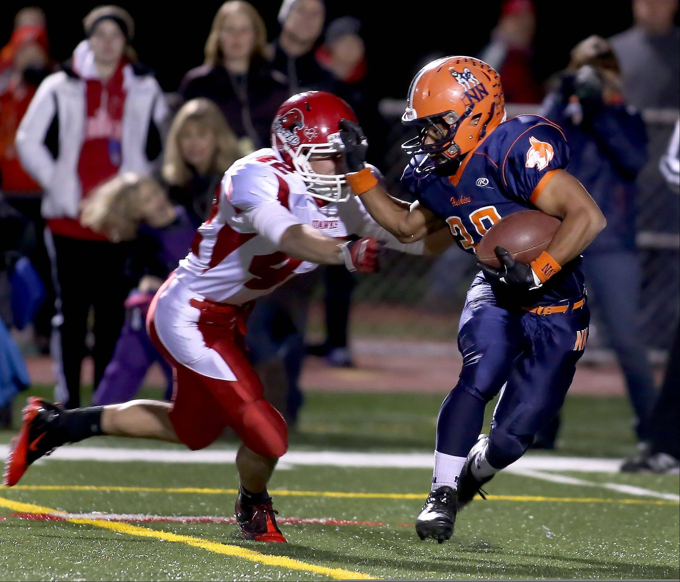 Daniel Spaccapaniccia of Naperville Central moves in to tackle Adam Milsap of Naperville North, right, during football action on Friday at North Central College.