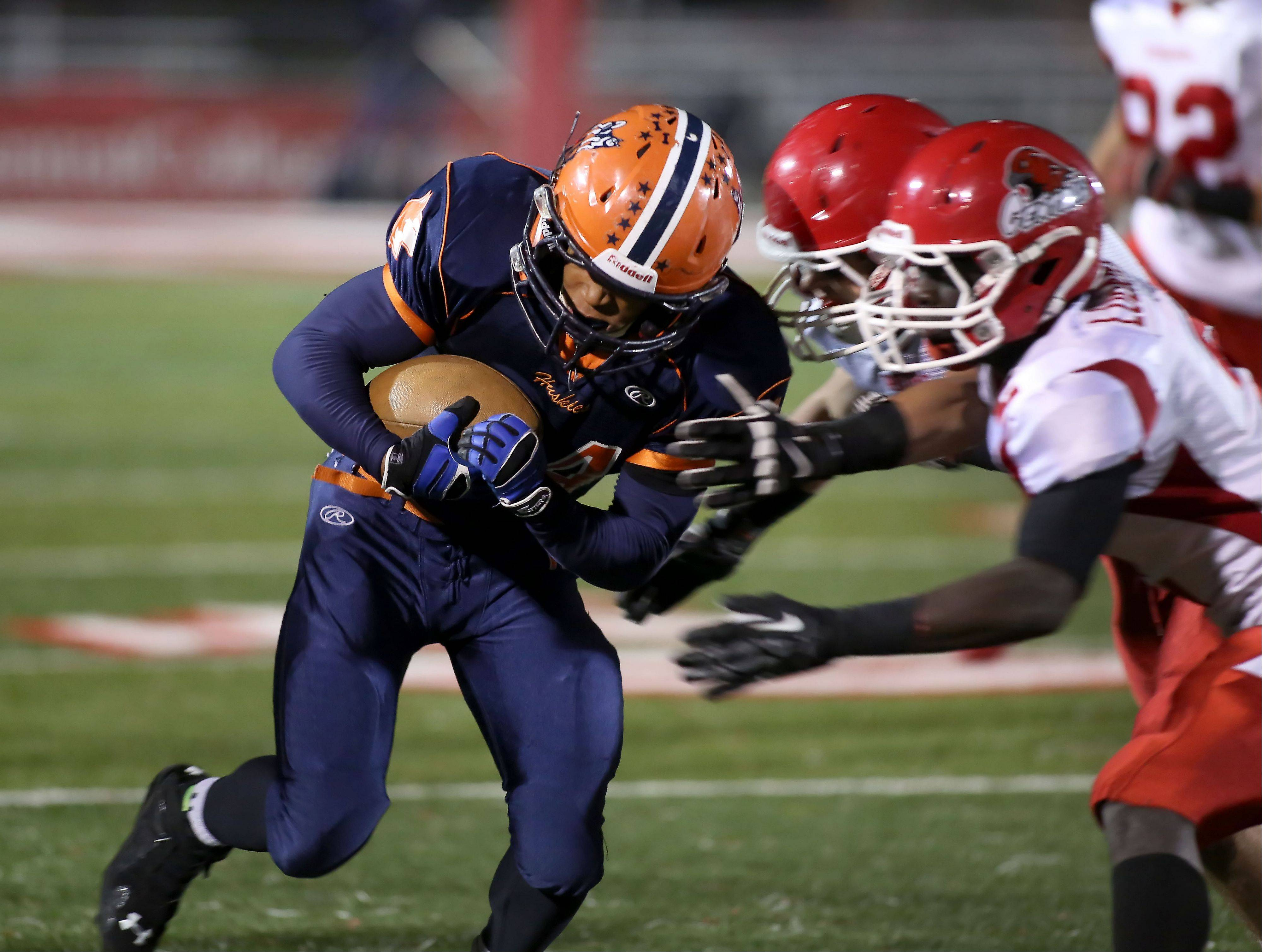 Sharad Crosby of Naperville North, left, tries to evade Naperville Central defense in football action on Friday at North Central College.