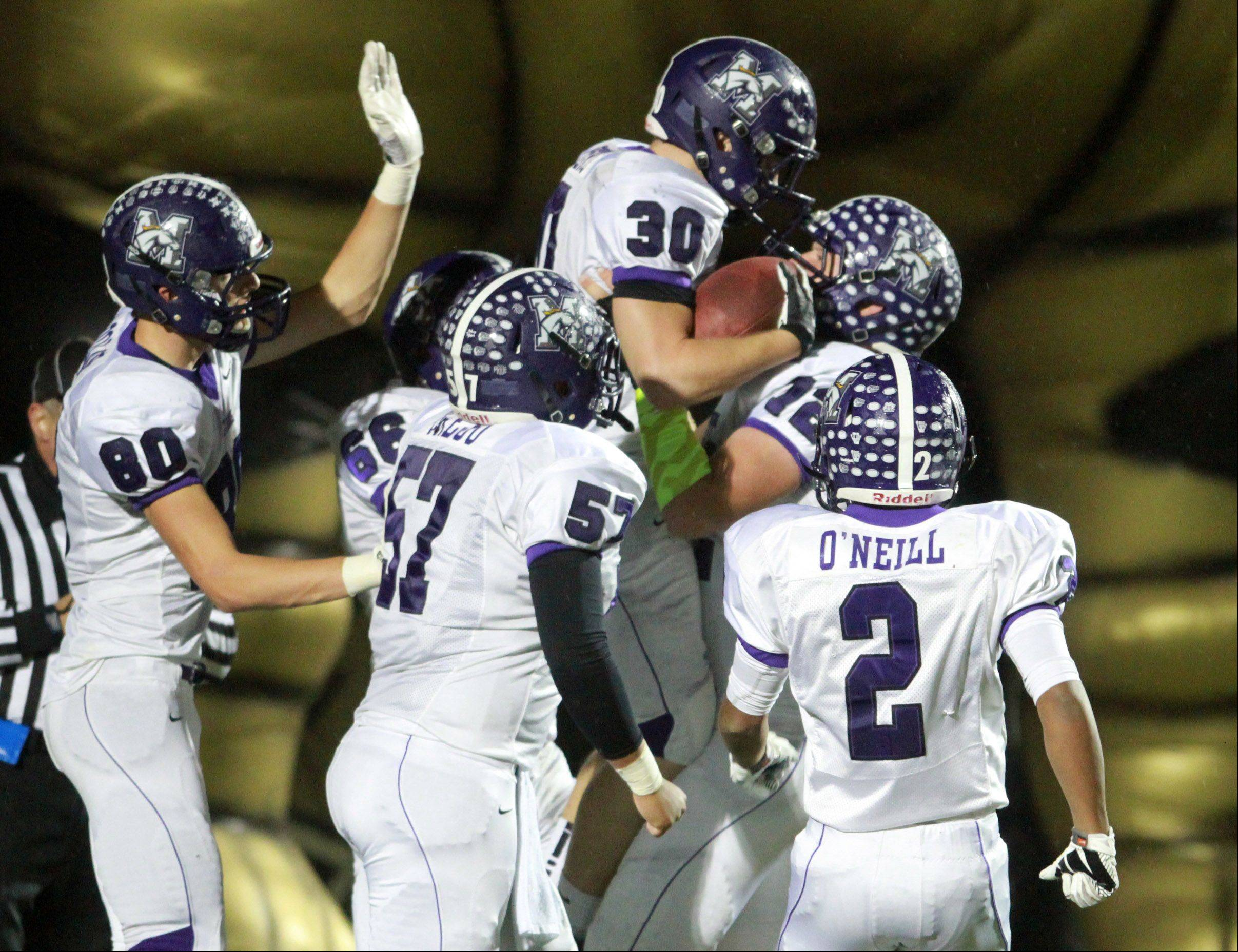 After scoring a touchdown, Rolling Meadows' Kevin Montero leaps into the arms of offensive lineman Greg Off in a Class 6A playoff opener at Grayslake North on Friday.