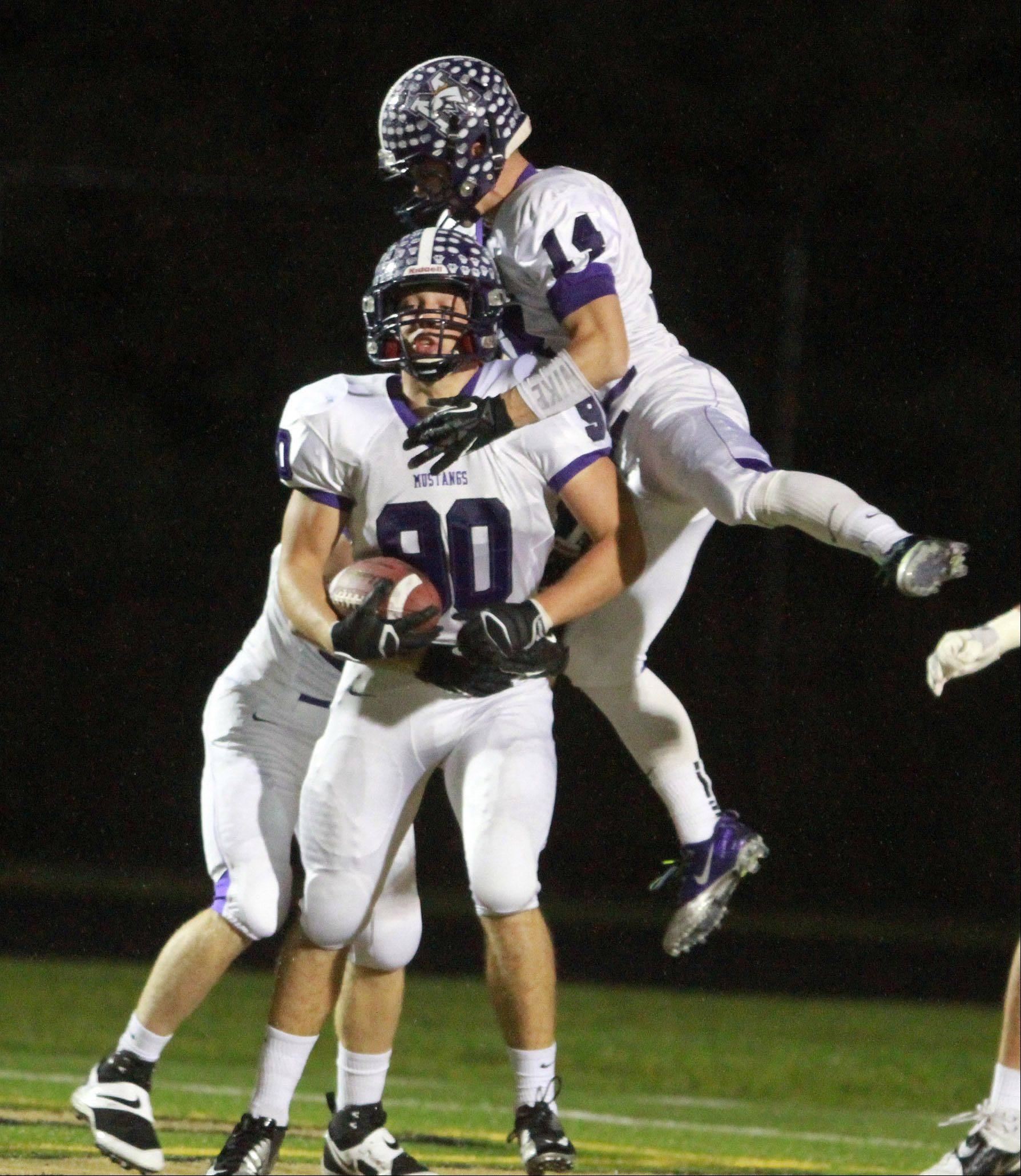 Rolling Meadows' players Alex Niecikowski, right, and Matt Campbell, left, celebrate a Campbell touchdown at Grayslake North on Friday.