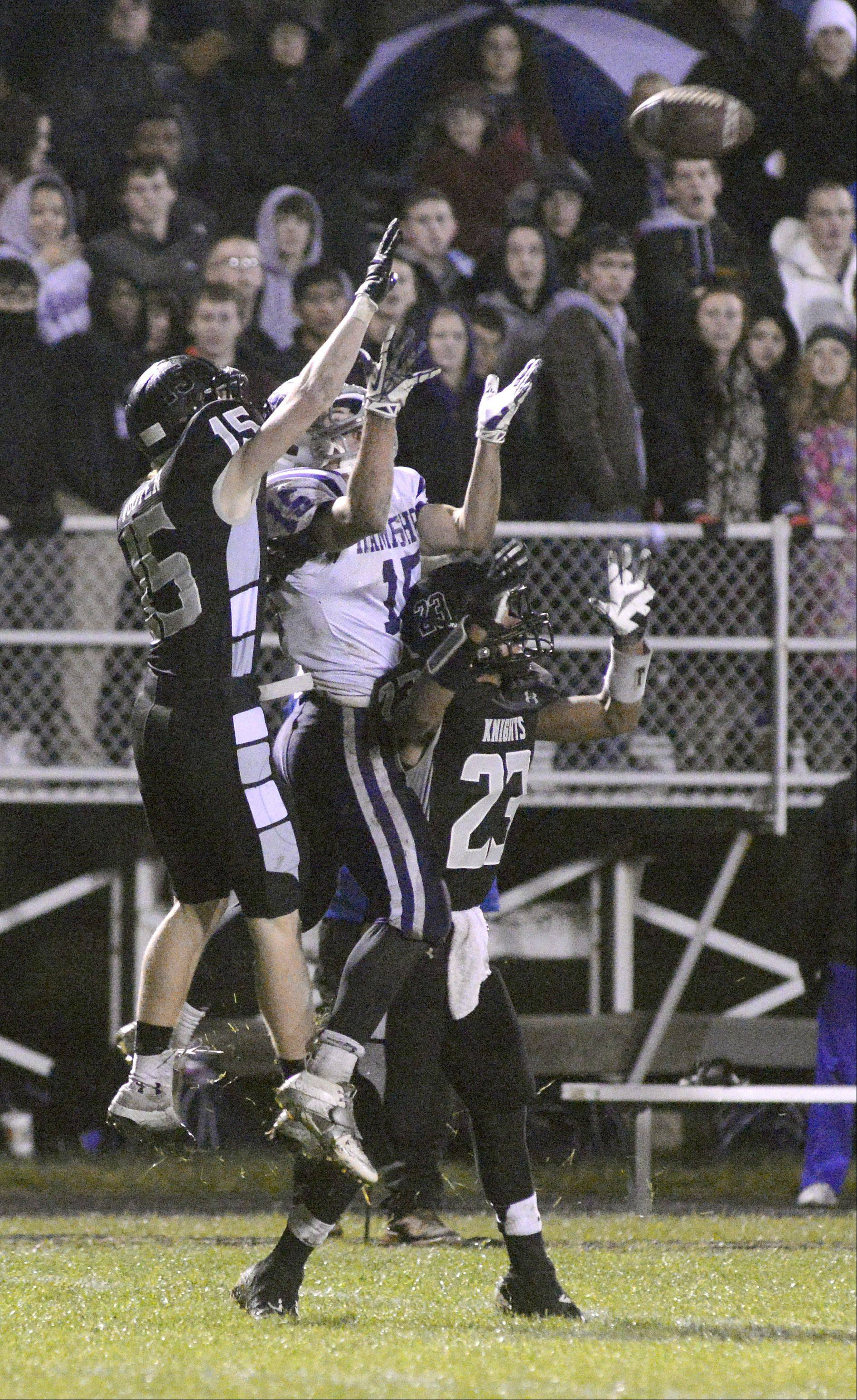 Kaneland's Alex Aurelio (15) and Isaac Swithers (23) leap in tandem for the ball with Hampshire's Tim Jansen in the second quarter, the ball slipping through all their fingers, on Friday, November 1.