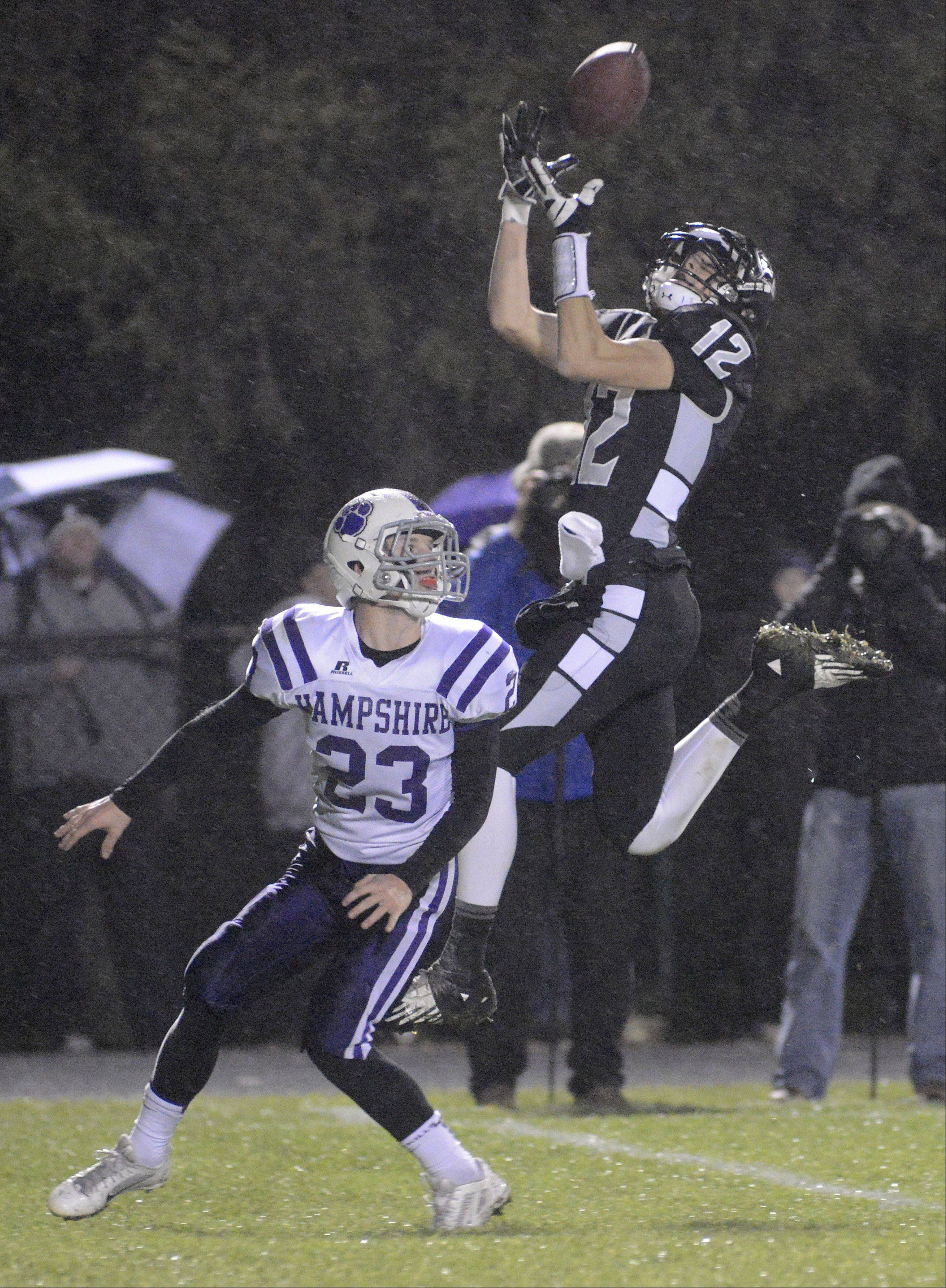 Laura Stoecker/lstoecker@dailyherald.com Kaneland's John Pruett leaps to complete a pass, but is taken down momentarily by Hampshire's Trey Schramm in the first quarter on Friday, November 1.