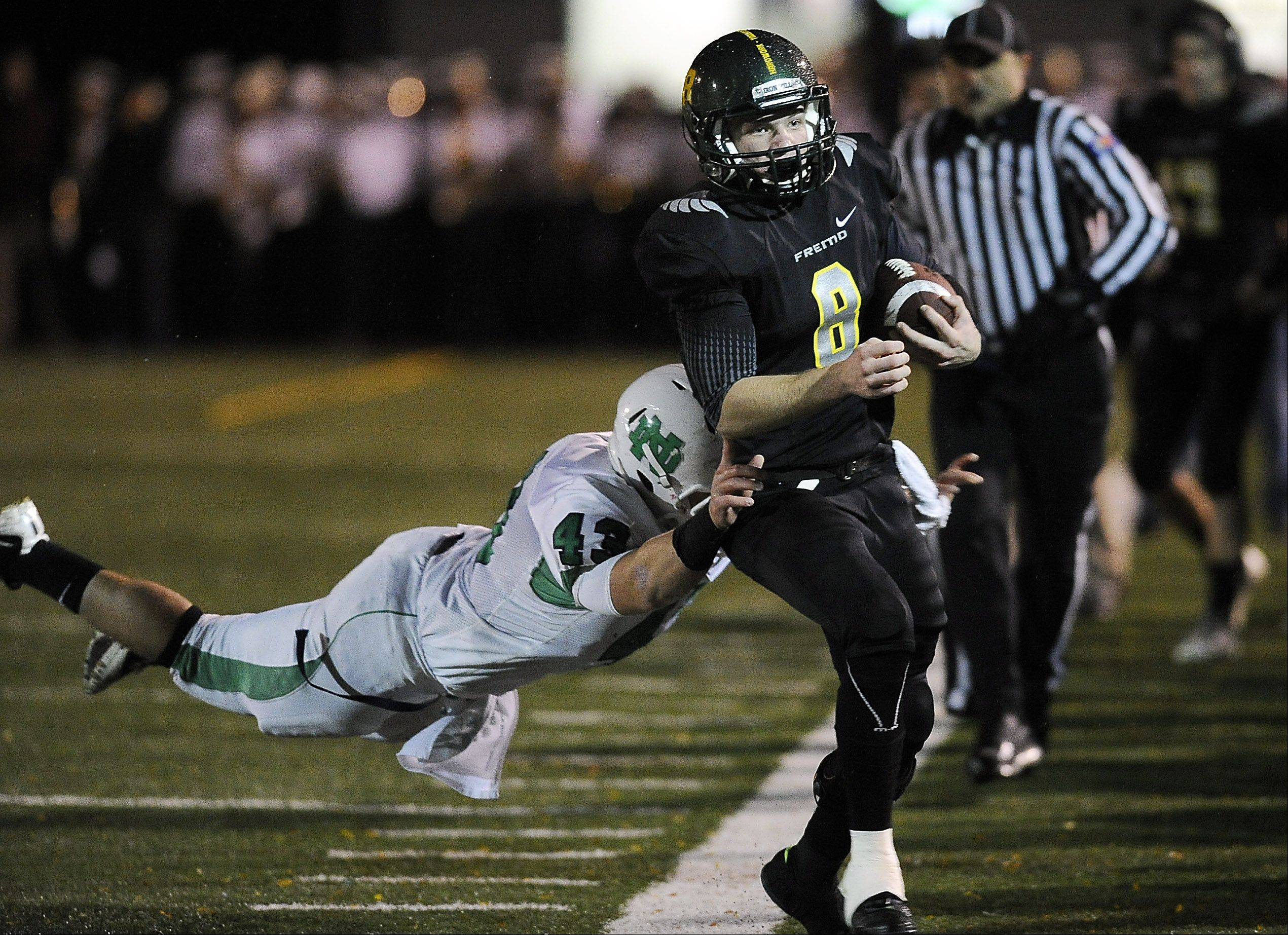 Fremd's Sam Beutler picks up 8 yards on this run as he is forced out of bounds by Notre Dame's Matt Kuszynski in the first half in Palatine on Friday.