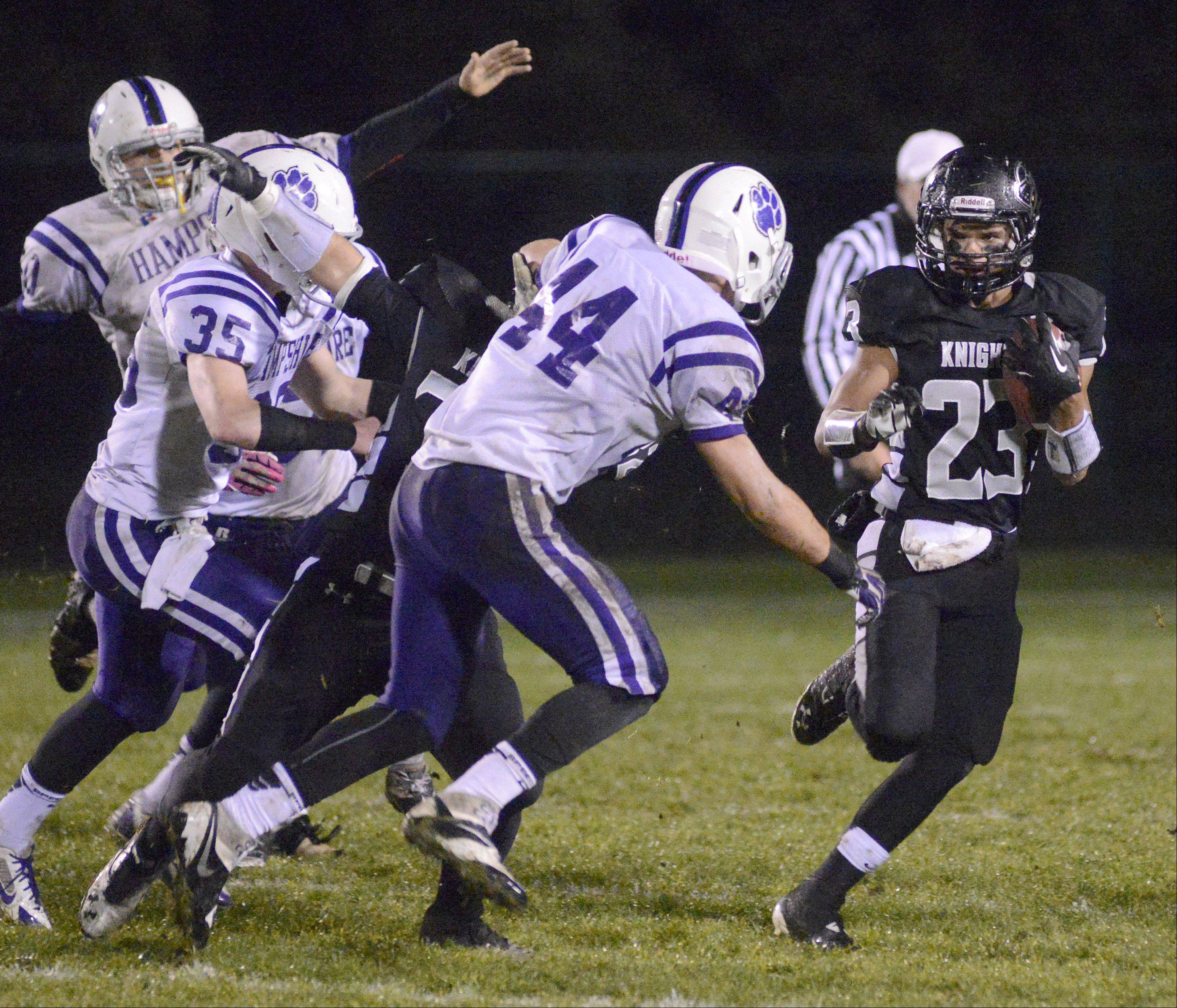 Kaneland's Gio Regalado steers clear of Hampshire's Mason Fleury in the first quarter .