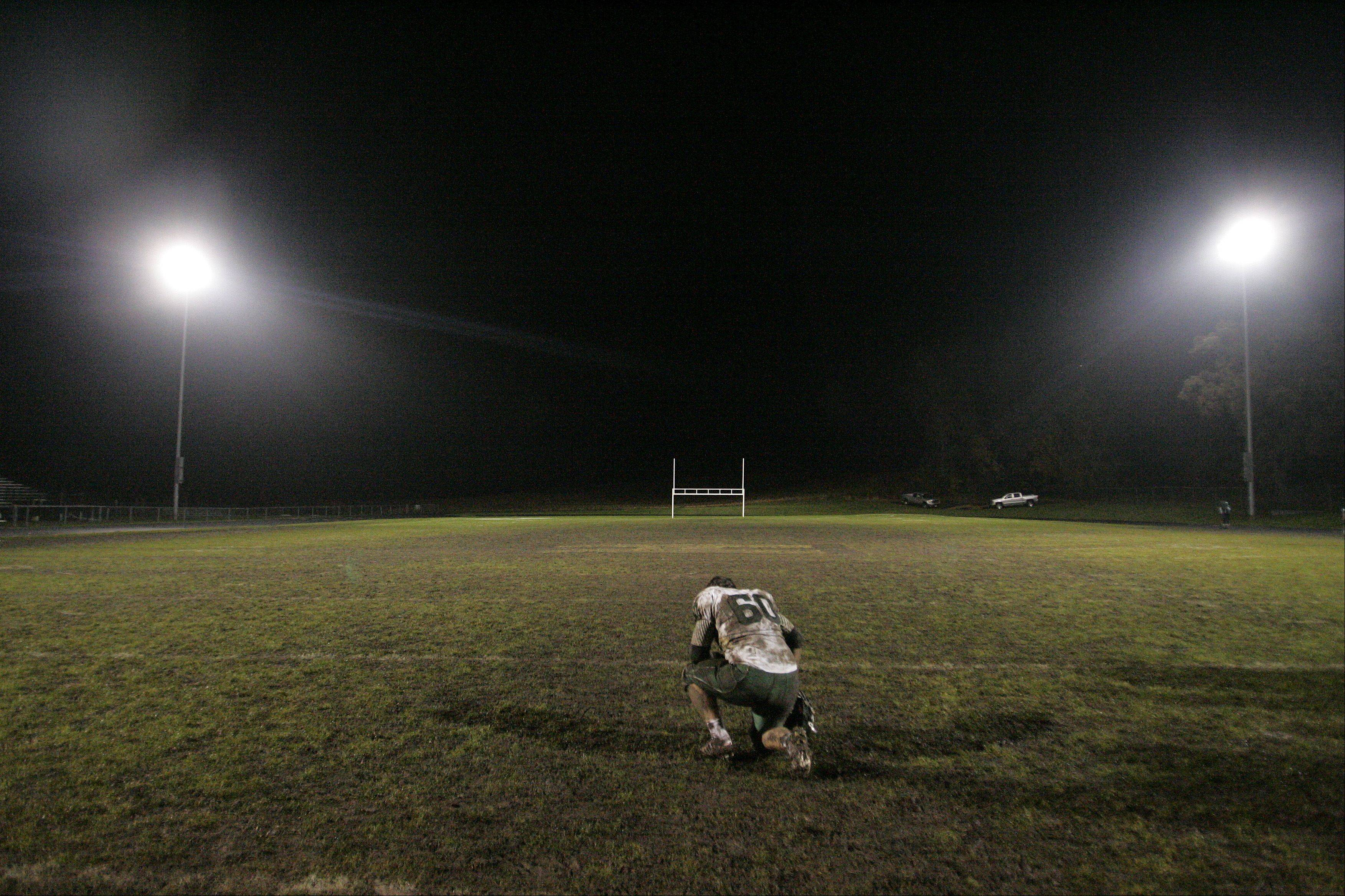 St. Edward's Zach West (60) collects himself after their loss against Harvard during the IHSA Class 4A playoff game Friday.
