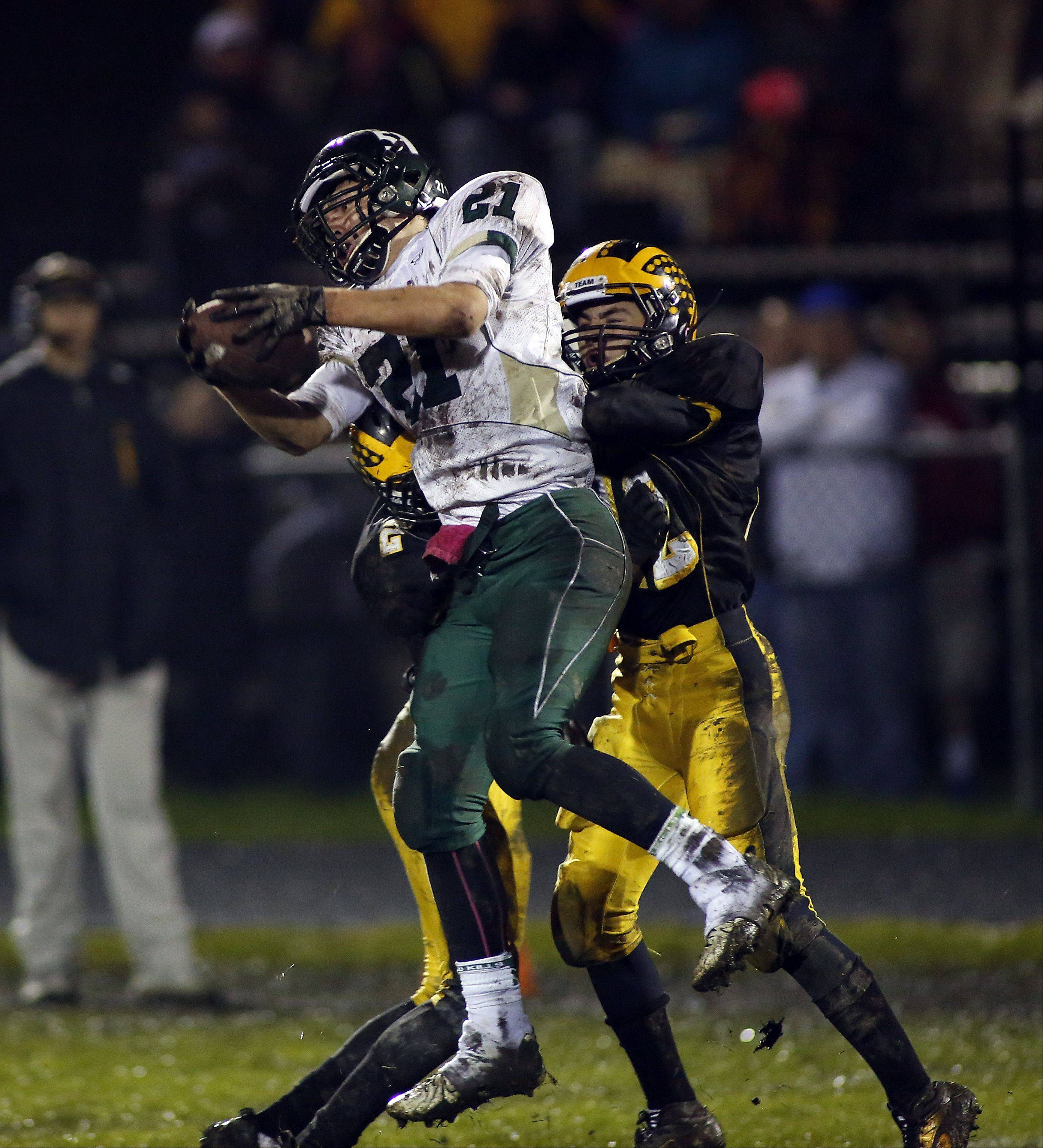 St. Edward's Danny Favela (21) reels in a long touchdown pass at Harvard during the IHSA Class 4A playoff game Friday.