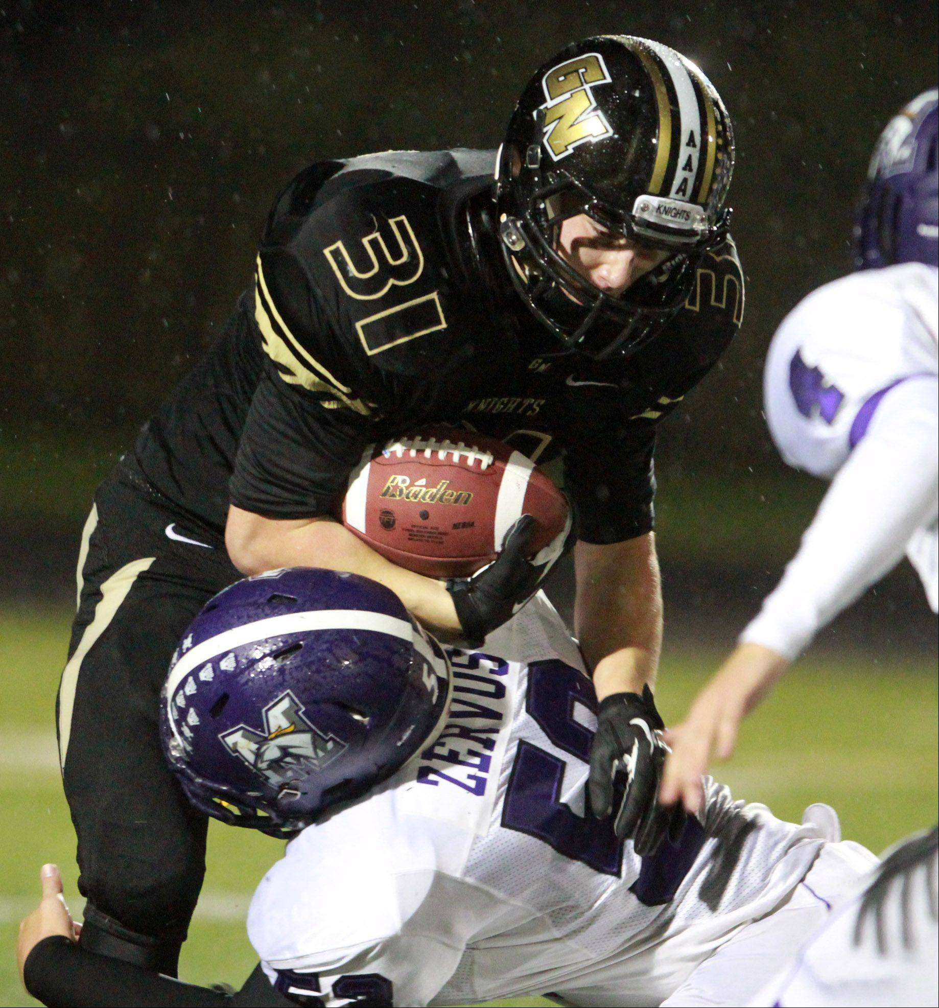 Rolling Meadows defender Manny Zervos pulls down against Grayslake North wide receiver Brad Baker.
