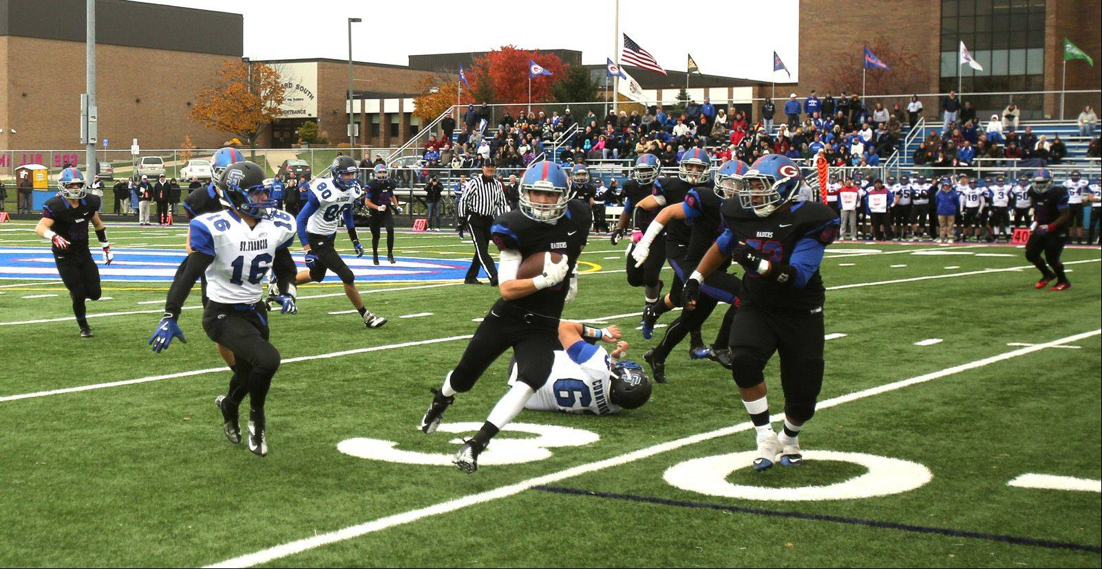 Glenbard South's Jack Curtis looks for yardage after intercepting a late fourth quarter pass against St. Francis.