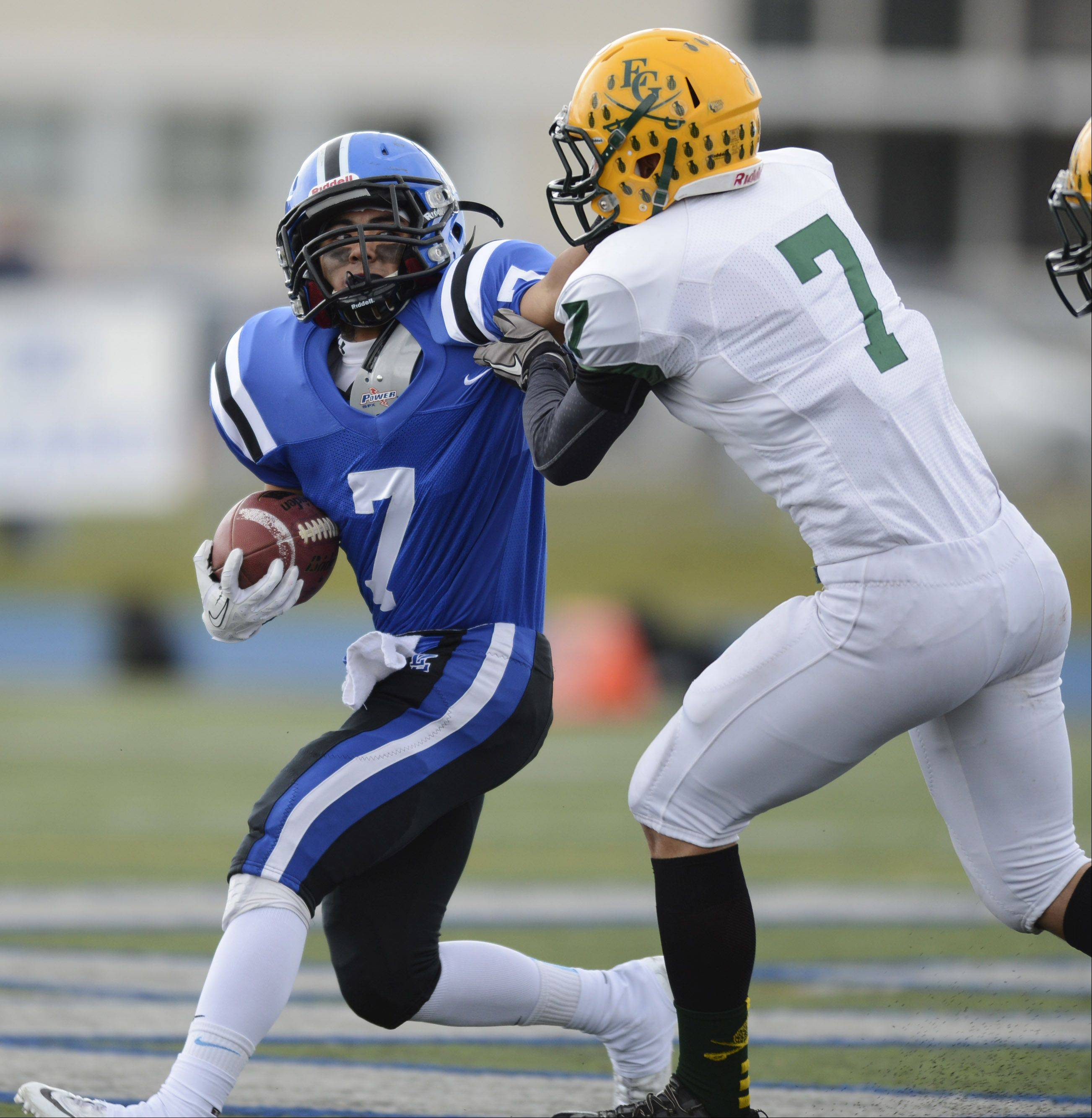 Lake Zurich's Mark Lacsam, left, gets tackled by Elk Grove's Nicolas Quirindongo during Saturday's Class 7A playoff game.