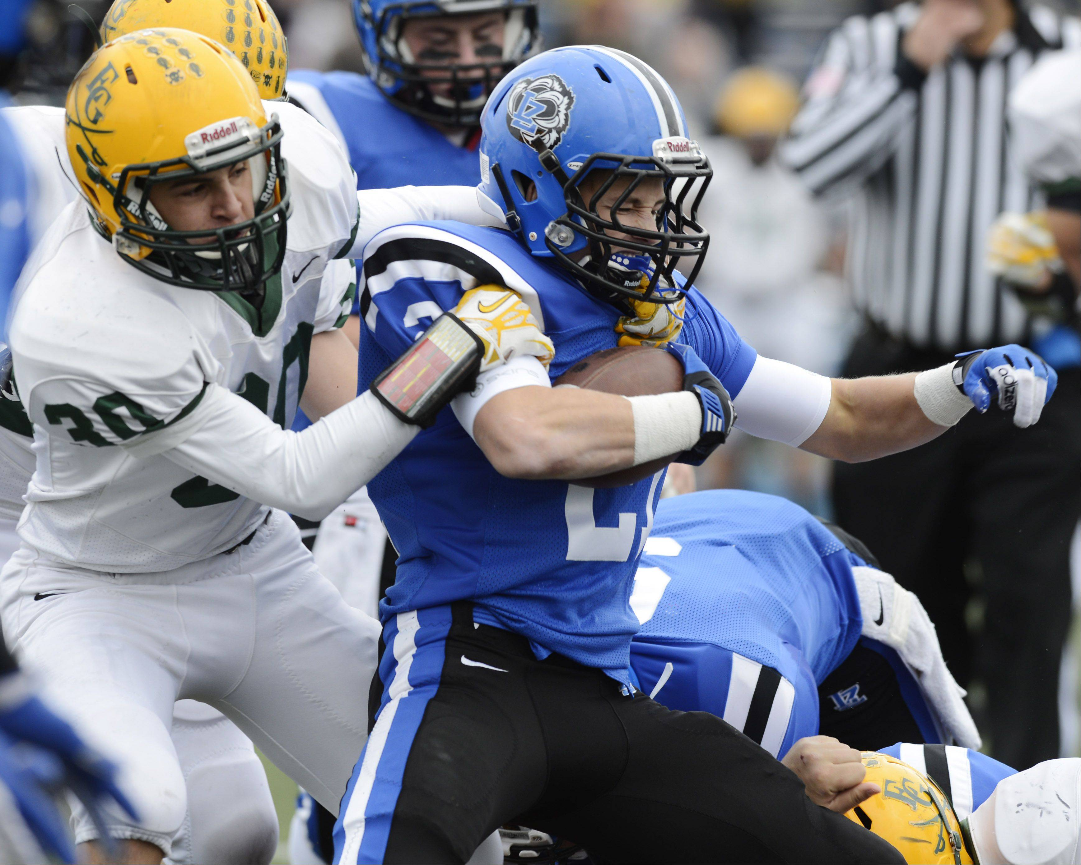 Lake Zurich's Dylan Schassler gets tackled by Elk Grove's Brandon Post during Saturday's Class 7A playoff game.