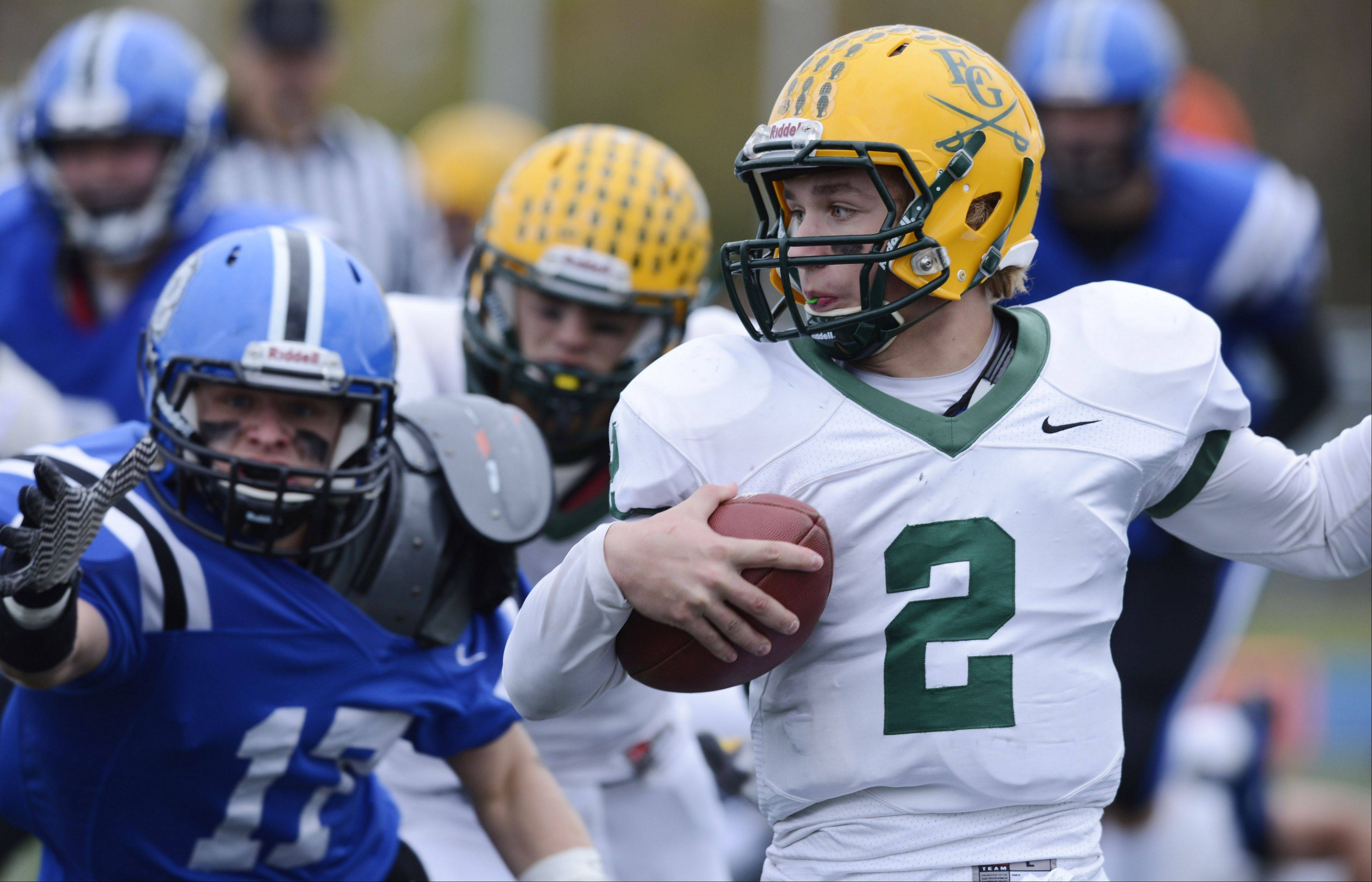 Elk Grove's quarterback Adam O'Malley carries the ball as Lake Zurich's Anthony Baca closes in during Saturday's Class 7A playoff game.
