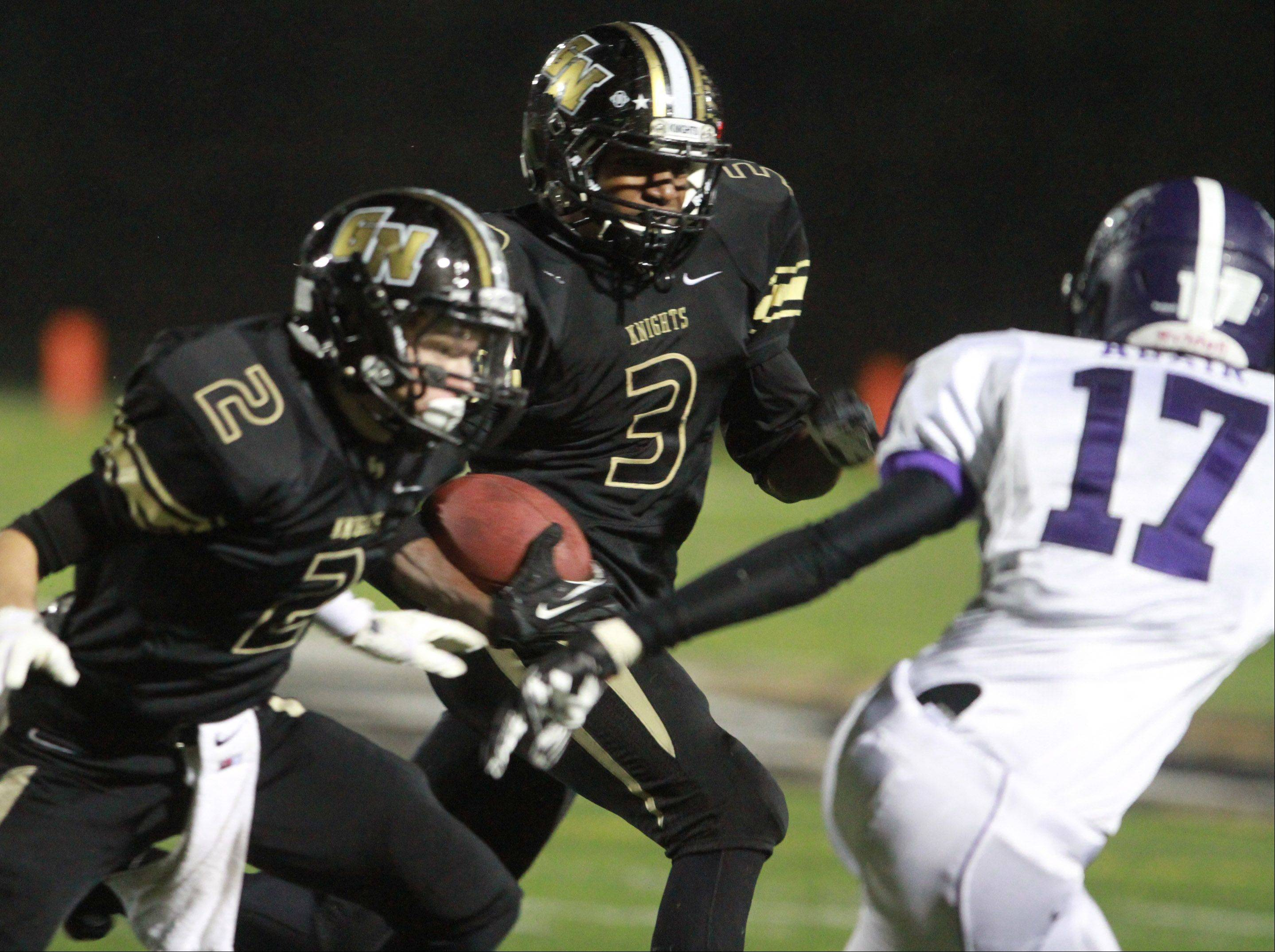 Grayslake North's Titus Booker looks for running room as Dylan Foster (2) looks to block a defender against Rolling Meadows last Friday night.