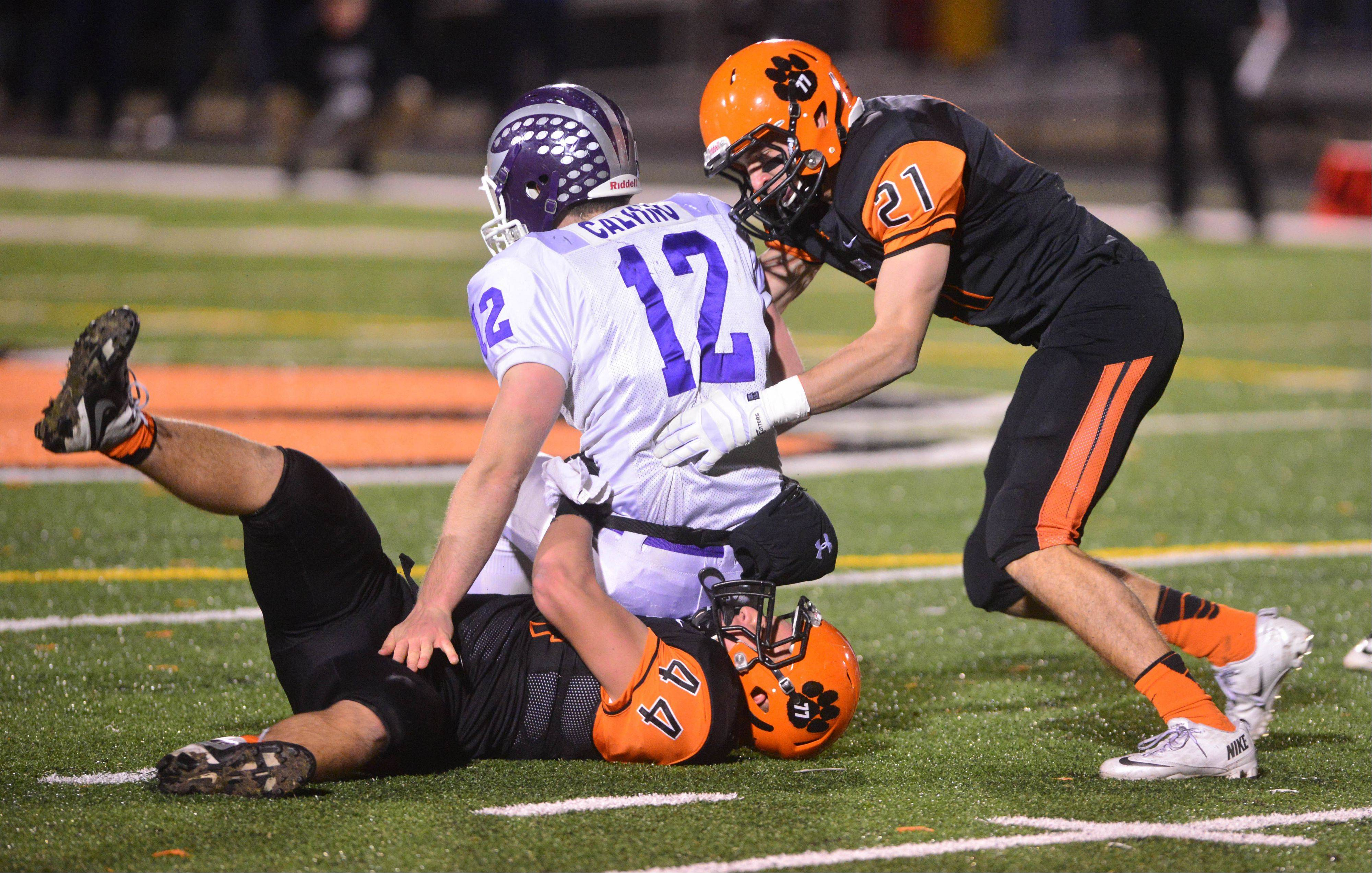 Sebastian Calvino of Downers Grove North is pulled down by defenders Joseph Machalek,left, and Jake Schultz of Wheaton Warrenville South .
