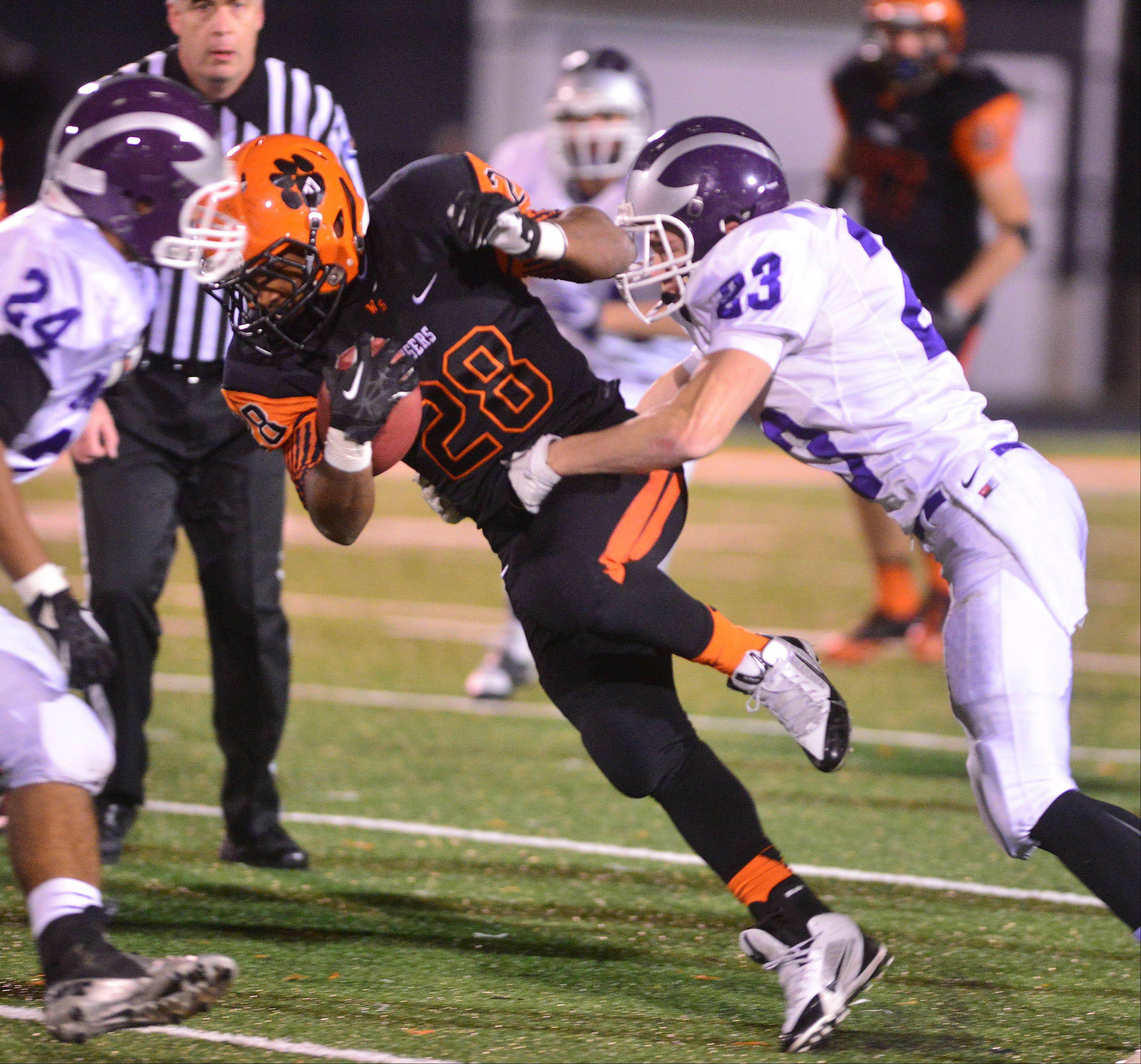 Isaiah Campos of Wheaton Warrenville South breaks a tackle from Mitchell Coha.