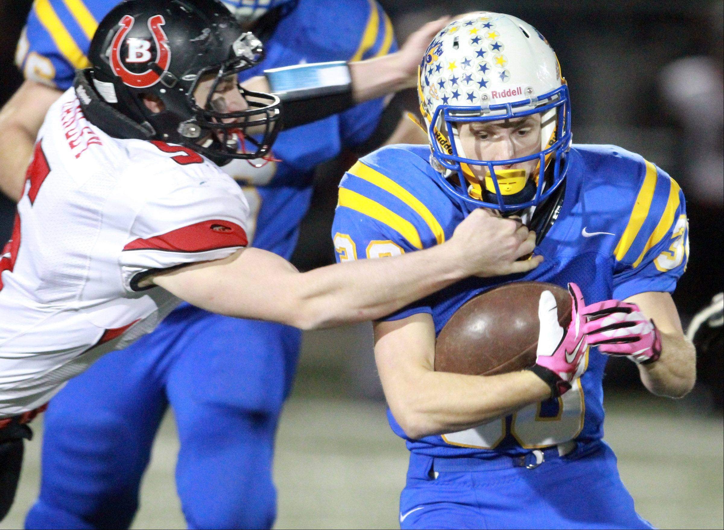 George LeClaire/gleclaire@dailyherald.com Warren running back Maxwell Sorby is dragged down by Barrington defender Dan Hanley in the first half Saturday in Gurnee.