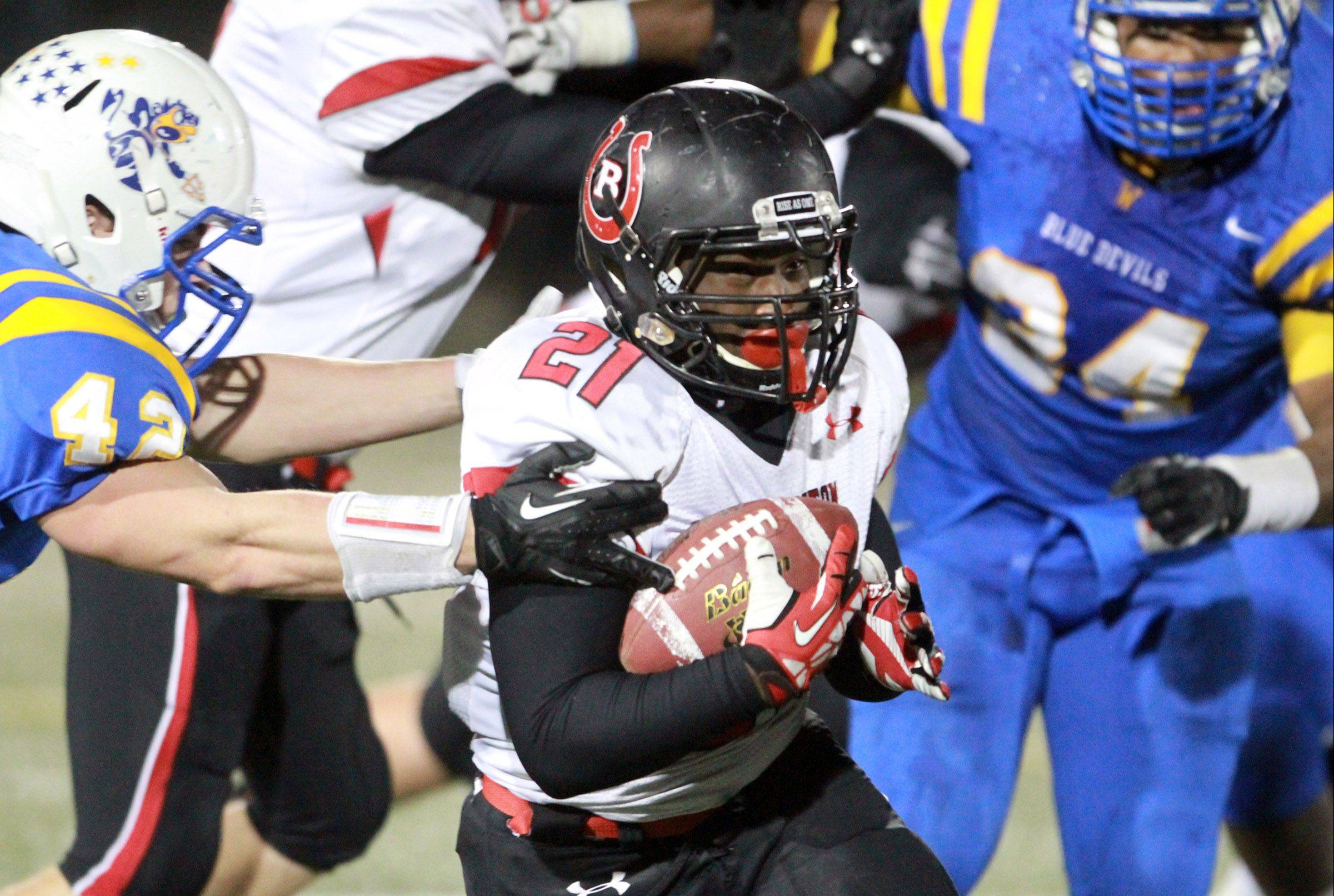 Barrington running back Nate King slips past Warren defender Lucus Fulton, left, in the first half of the Class 8A playoffs Saturday in Gurnee.
