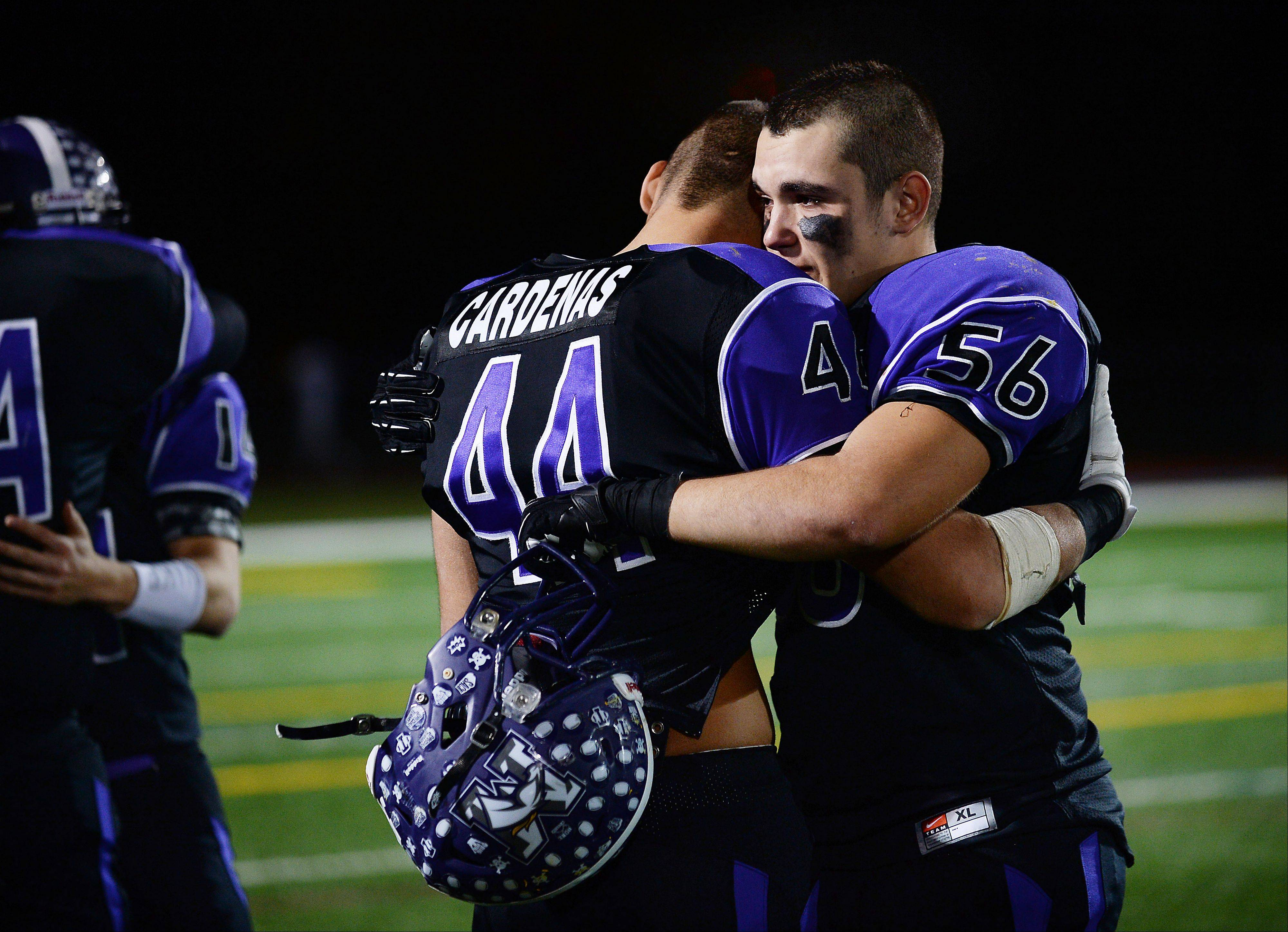 Rolling Meadows players Eddie Cardenas and George Someris embrace following Saturday's playoff loss to Batavia.