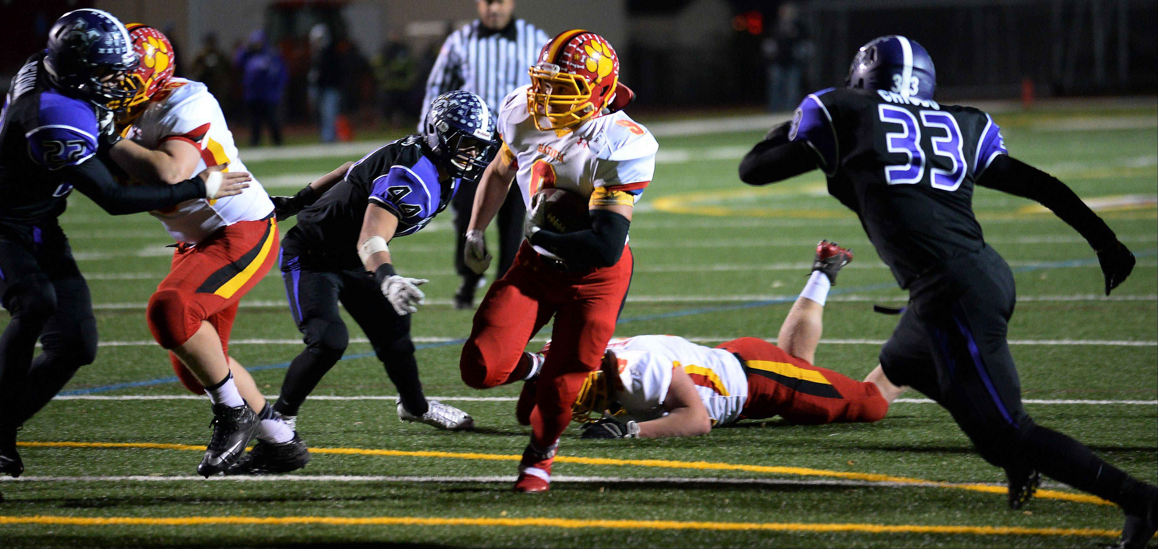 Batavia's Anthony Moneghini runs past Rolling Meadows' Nico Chiodo for a fourth-quarter touchdown in the second round of the Class 6A playoffs at Rolling Meadows on Saturday.