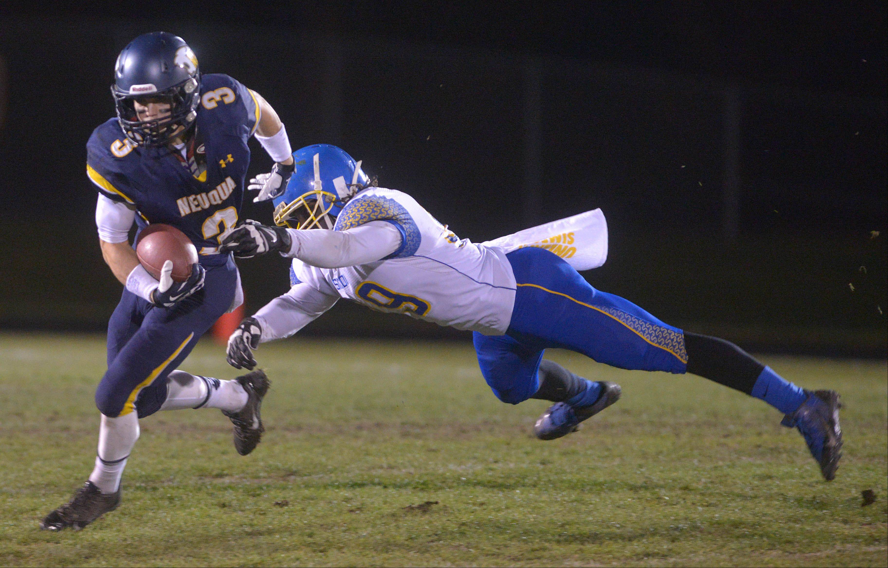 Neuqua Valley's Mikey Dudek gets past Simeon's Karlin Entoe Saturday's football playoff game.
