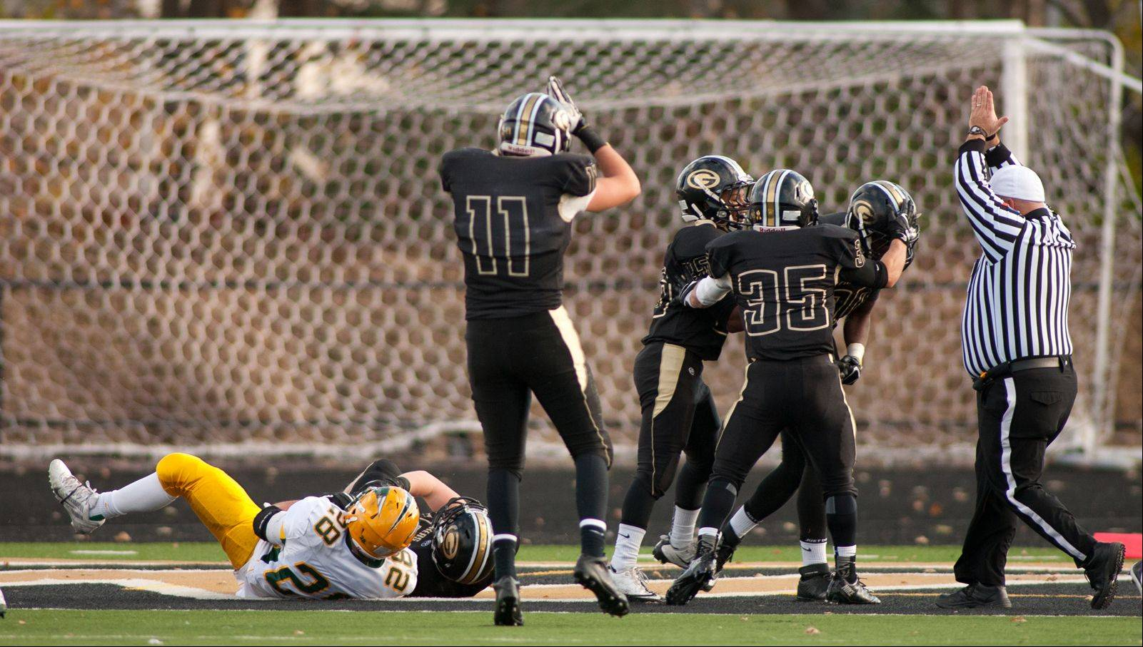 Glenbard North players celebrate scoring a safety against Stevenson punter Jack Joseph (28), who attempts to secure an errant snap. The play gave the Panthers a 16-14 lead.